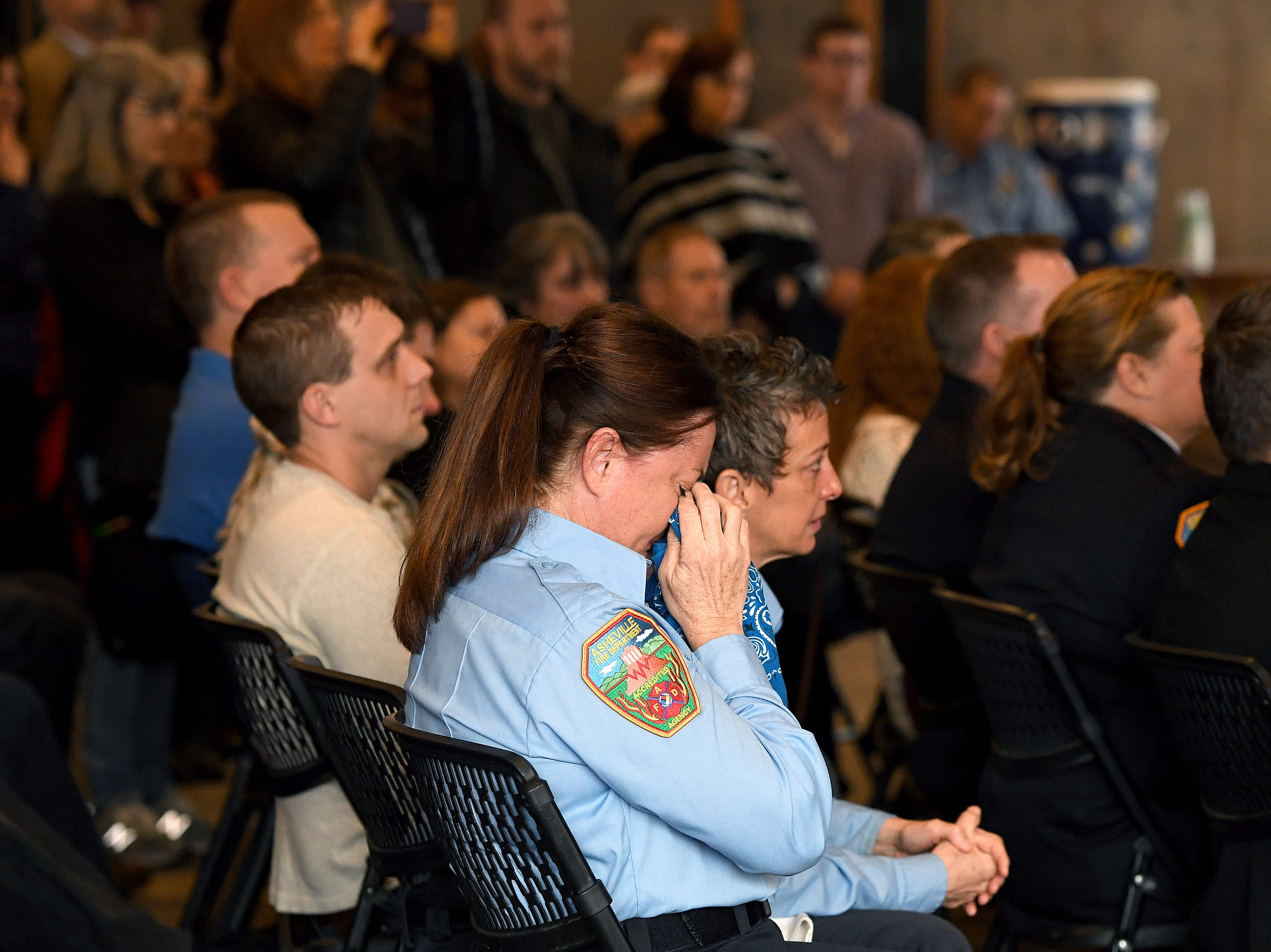 "A member of the Asheville Fire Department becomes emotional during a memorial service at the Salvage Station on Feb. 15, 2019 for the firefighter who died of cancer last month. Shuart died of cancer, the second cancer-related death in the department in a year. Her death is being considered an ""line-of-duty"" death."