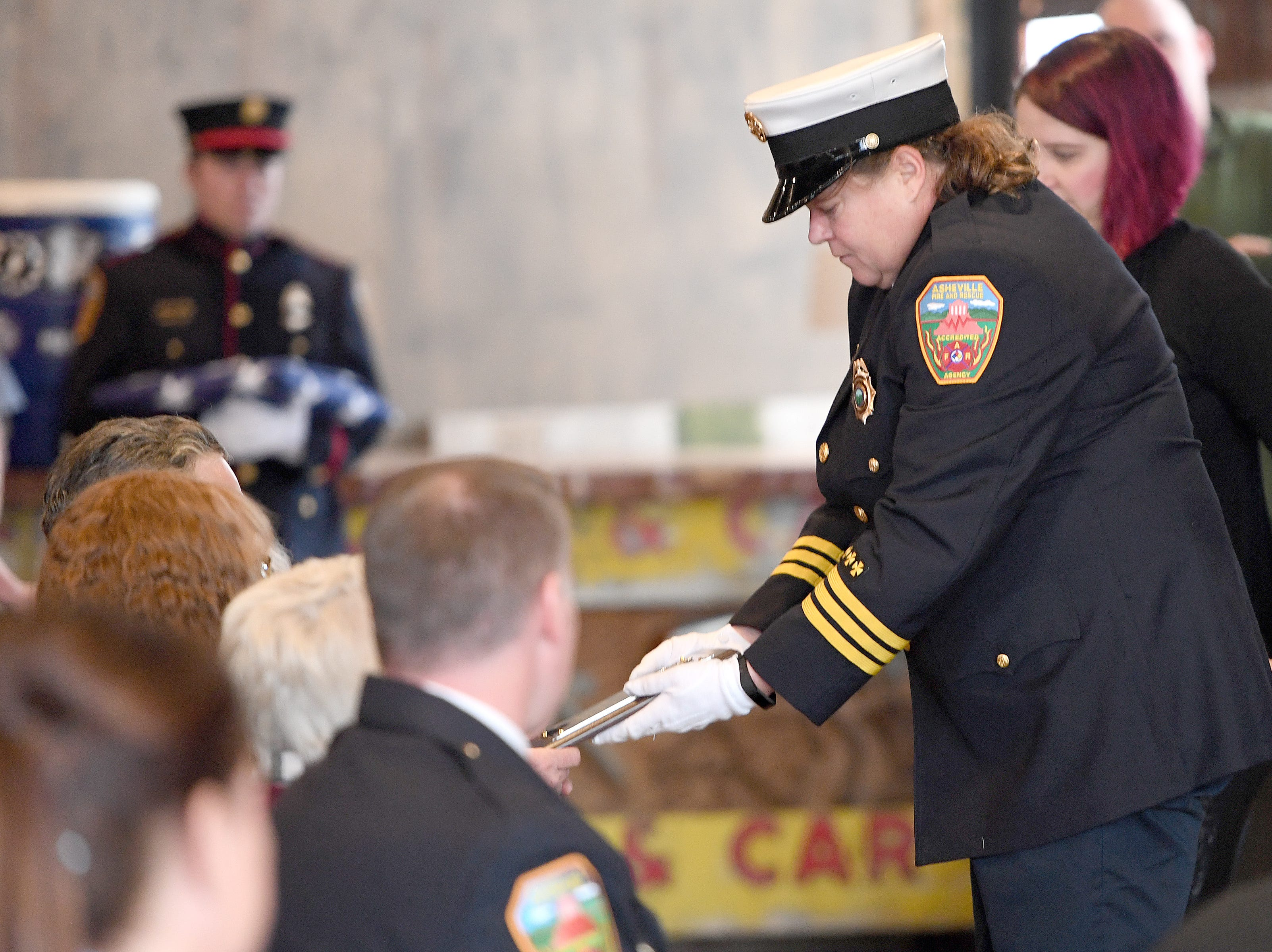 "Asheville Fire Marshall Kelly Hinz presents Karen Shuart's family with a plaque commemorating her 25 years with the department during a memorial service at the Salvage Station on Feb. 15, 2019 for the firefighter who died of cancer last month. Shuart died of cancer, the second cancer-related death in the department in a year. Her death is being considered an ""line-of-duty"" death."