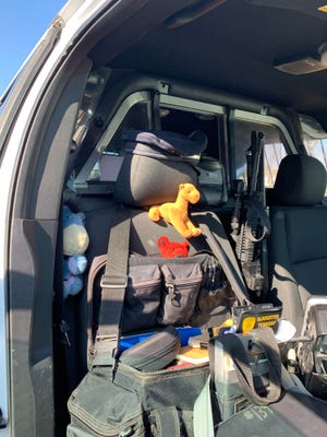 A plush camel, teddy bear and a stuffed Eeyore are secured in a police cruiser next to a police rifle.