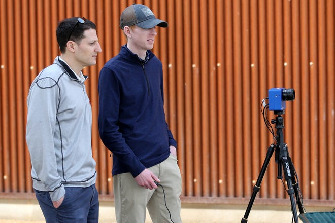 Cincinnati Reds assistant general manager Sam Grossman, left, and director of advanced scouting Bo Thompson, center, observe a slow motion camera while it films pitchers throwing during a bullpen session, Friday, Feb. 15, 2019, at the Cincinnati Reds spring training facility in Goodyear, Arizona.