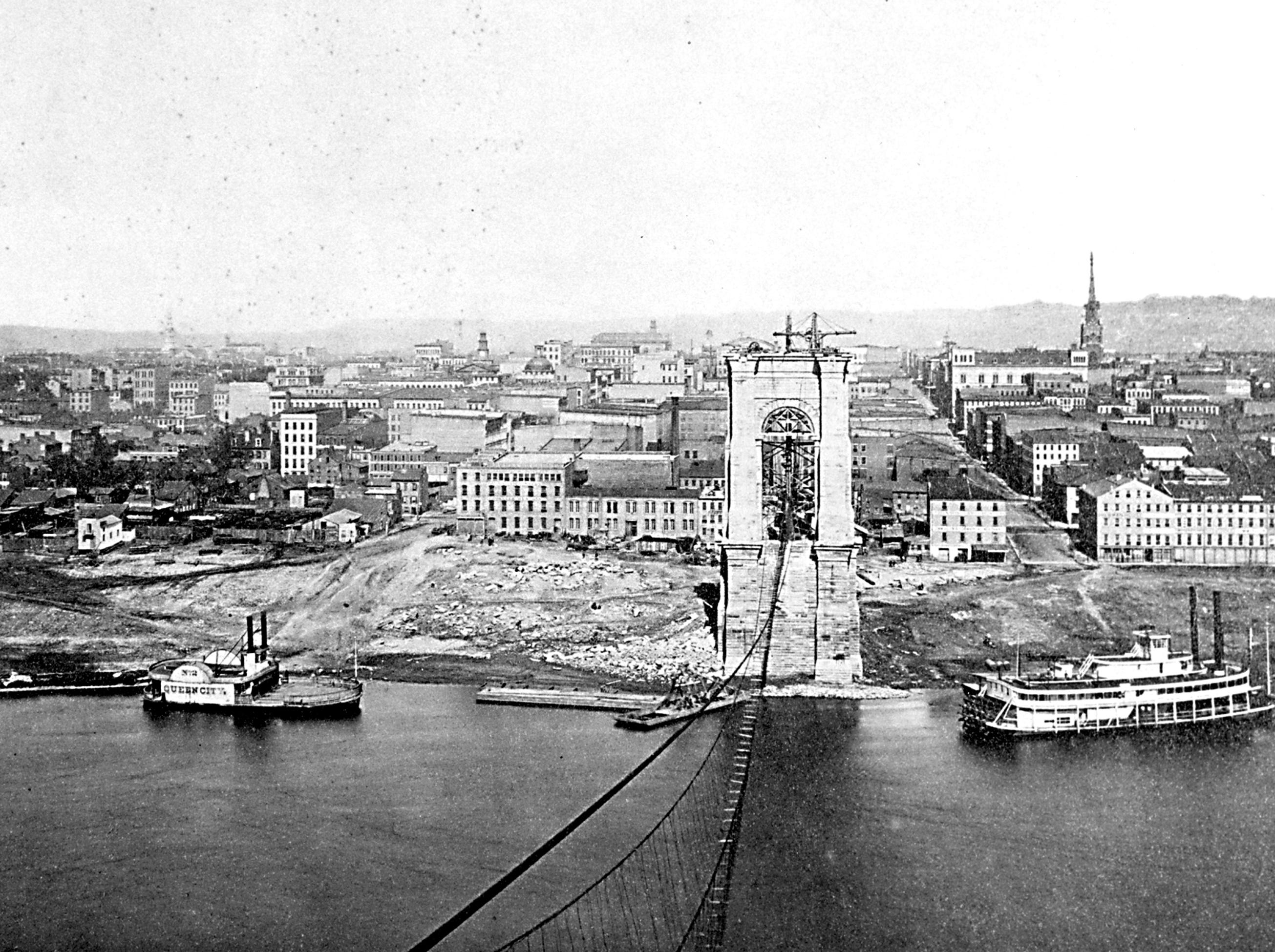 """The incomplete Roebling Suspension Bridge, as seen Oct. 4, 1865. Provided/Cincinnati Museum Center 19th Century 033 SUBJECT: BRIDGES.  SUSPENSION BRIDGE DATE: OCT. 4, 1865 DONOR: JOSEPH R. STERN, 11--08-1965 NEG #'S: A-92-049, B-88-221 ORIG SIZE: 8"""" X 10"""", B&W SCAN DATE: 07-19-99 NOTES: ( ON BACK ); PHOTO OF INCOMPLETED SUSPENSION BRIDGE SHOWING THE FIRST CABLE WHICH HAD BEEN """"STRUNG OVER"""", AND THE """"FOOT BRIDGE"""" BELOW WHICH HAD JUST BEEN COMPLETED. OCTOBER 4, 1865. ALSO ON BACK- MAYHEW PHOTOGRAPHERS, 128 W. 5TH ST., CINCINNATI 2, OHIO. REORDER # A2646"""