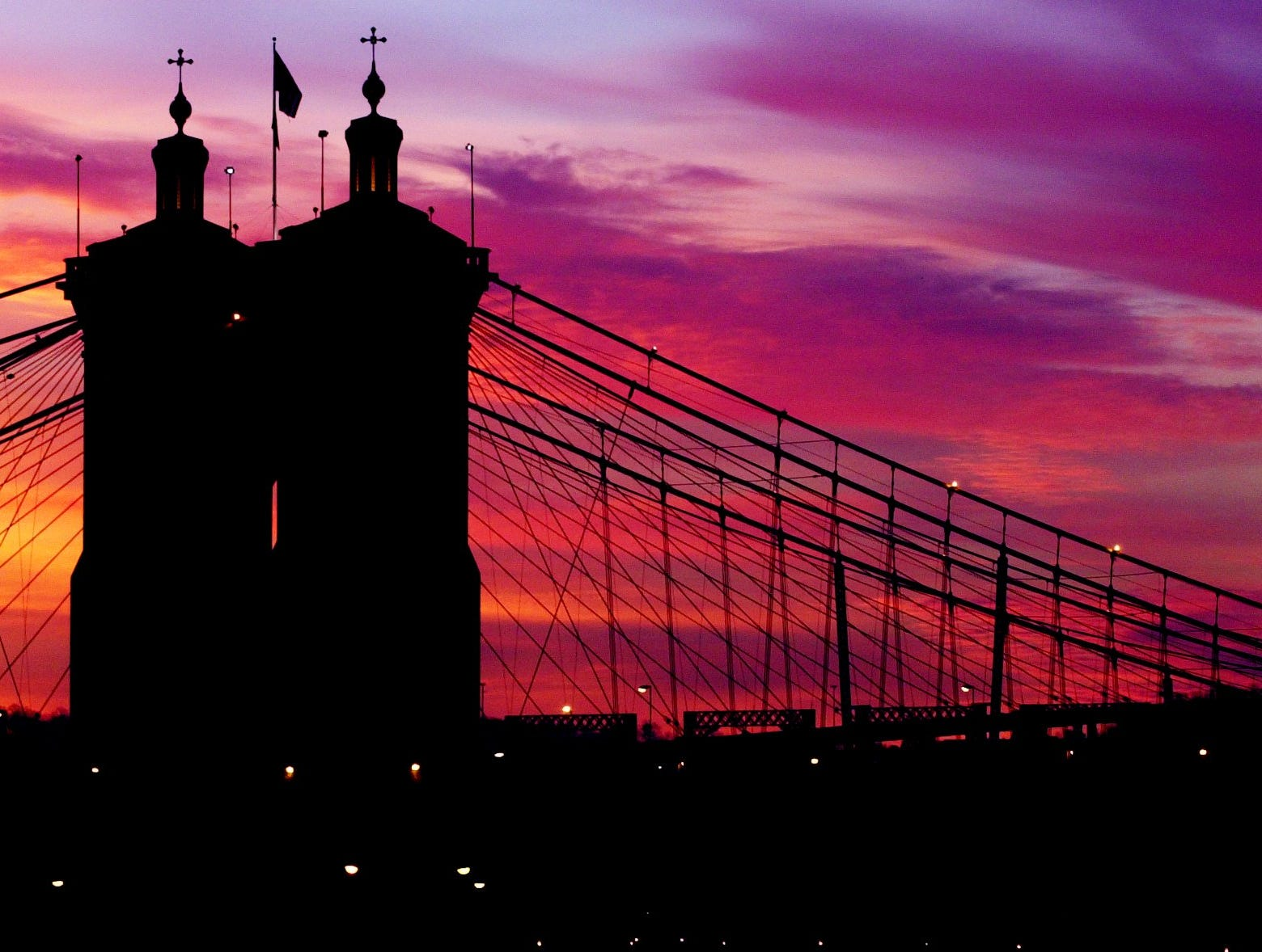 2002.12.29.12 IMPLOSION METRO: The Roebling Bridge is silhouetted against the sky as the sun rises just before Cinergy Field was imploded Sunday December 29, 2002. The Cincinnati Enquirer / Brandi Stafford .bs.