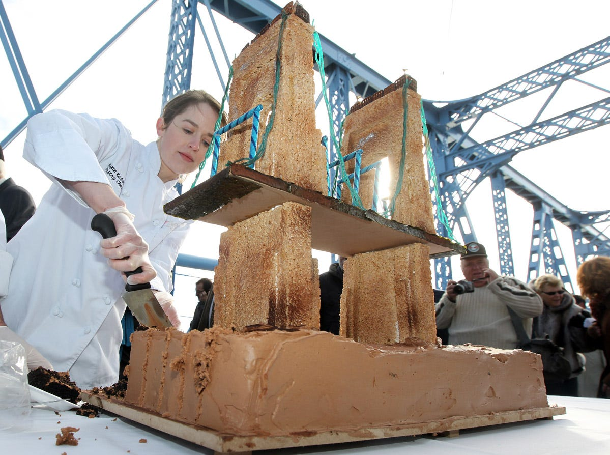 KY06ROEBLING KY NOVEMBER 5, 2010   Megan Ketover cuts a cake she made in the shape of the Roebling Suspension Bridge during a ceremony marking the re-opening of the bridge to vehicluar traffic.  She is the pastry chef at the Hilton Netherland Plaza.   The bridge has been closed to vehicular traffic since April for a $16.2 million painting project.  The Enquirer/Patrick Reddy