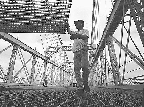 Text: steel worker david smith guides a new piece of grating into place as they rebuild parts of the deck on the joseph a. roebling suspension bridge over the ohio river in downtown cincinnati, tuesday july 23, 1996. the bridge, built in 1865, is undergoing renovations, which will include painting. (ap photo/the cincinnati post/tom uhlman)