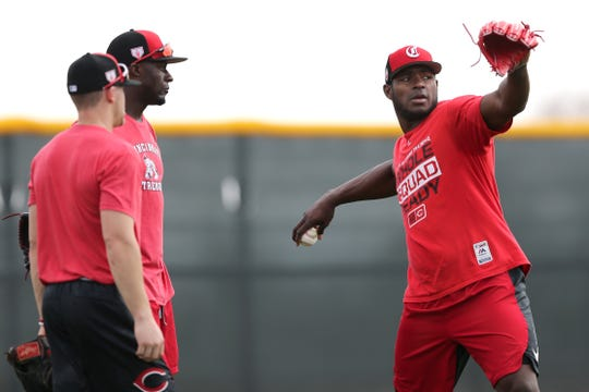 Cincinnati Reds right fielder Yasiel Puig (66), right, talks with Taylor Trammell, center, and TJ Friedl, left, during drills, Friday, Feb. 15, 2019, at the Cincinnati Reds spring training facility in Goodyear, Arizona.