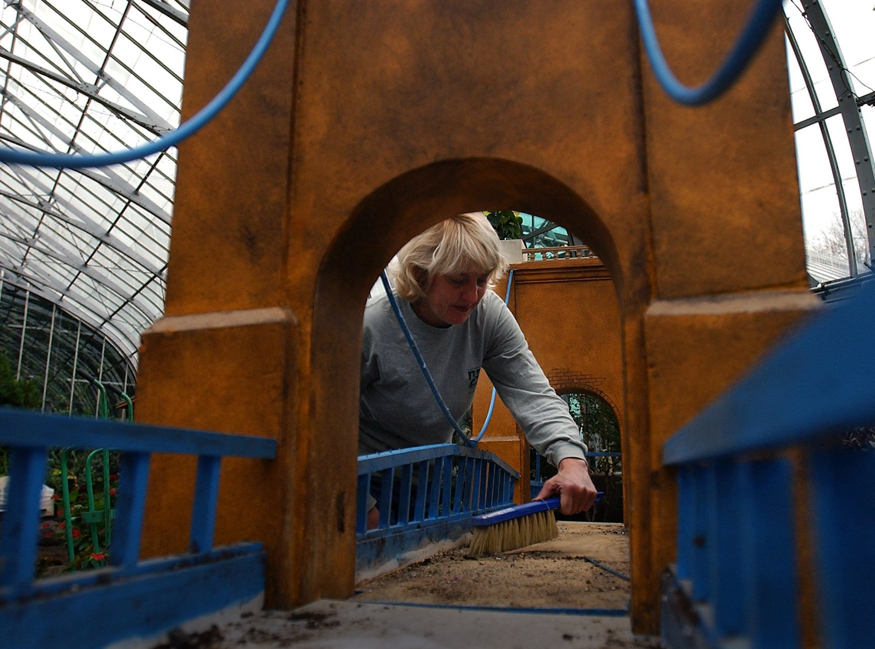 THURSDAY NOVEMBER 14, 2002 KROHN METRO Tracy Fryburger, a Krohn Conservatory designer, sweeps debris from a scale model of the Roebling Suspension Bridge. The annual holiday floral exhibit at Krohn Conservatory will feature Cincinnati landmarks amid floral displays. The exhibit opens November 22, 2002. Cincinnati Enquirer/Michael E. Keating mek
