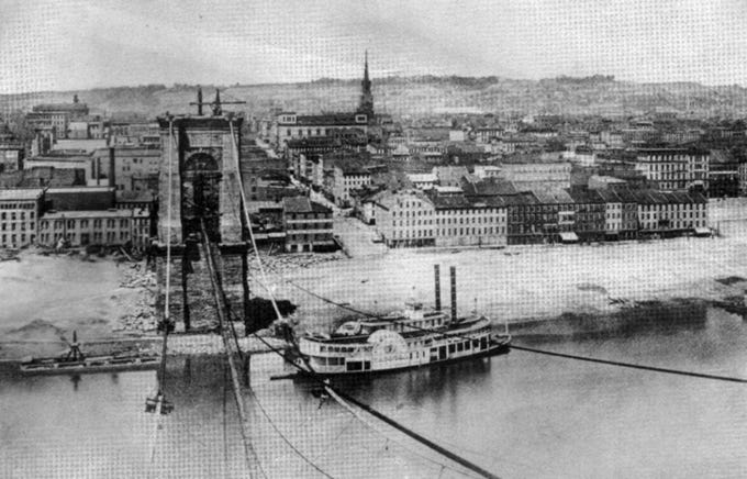 Construction of the Suspension Bridge over the Ohio River was delayed by the Civil War, but opened to pedestrian traffic Dec. 1, 1866. Enquirer FILE 1865: Construction of the Suspension Bridge over the Ohio River at Cincinnati in 1865. The street running north in the middle of the picture is Walnut Street. The bridge was begun in 1860 and completed in 1865. Reproduced by students in the Department of Lithography of the Mechanics Institute, 1938. From the Enquirer archives scanned December 20, 2010