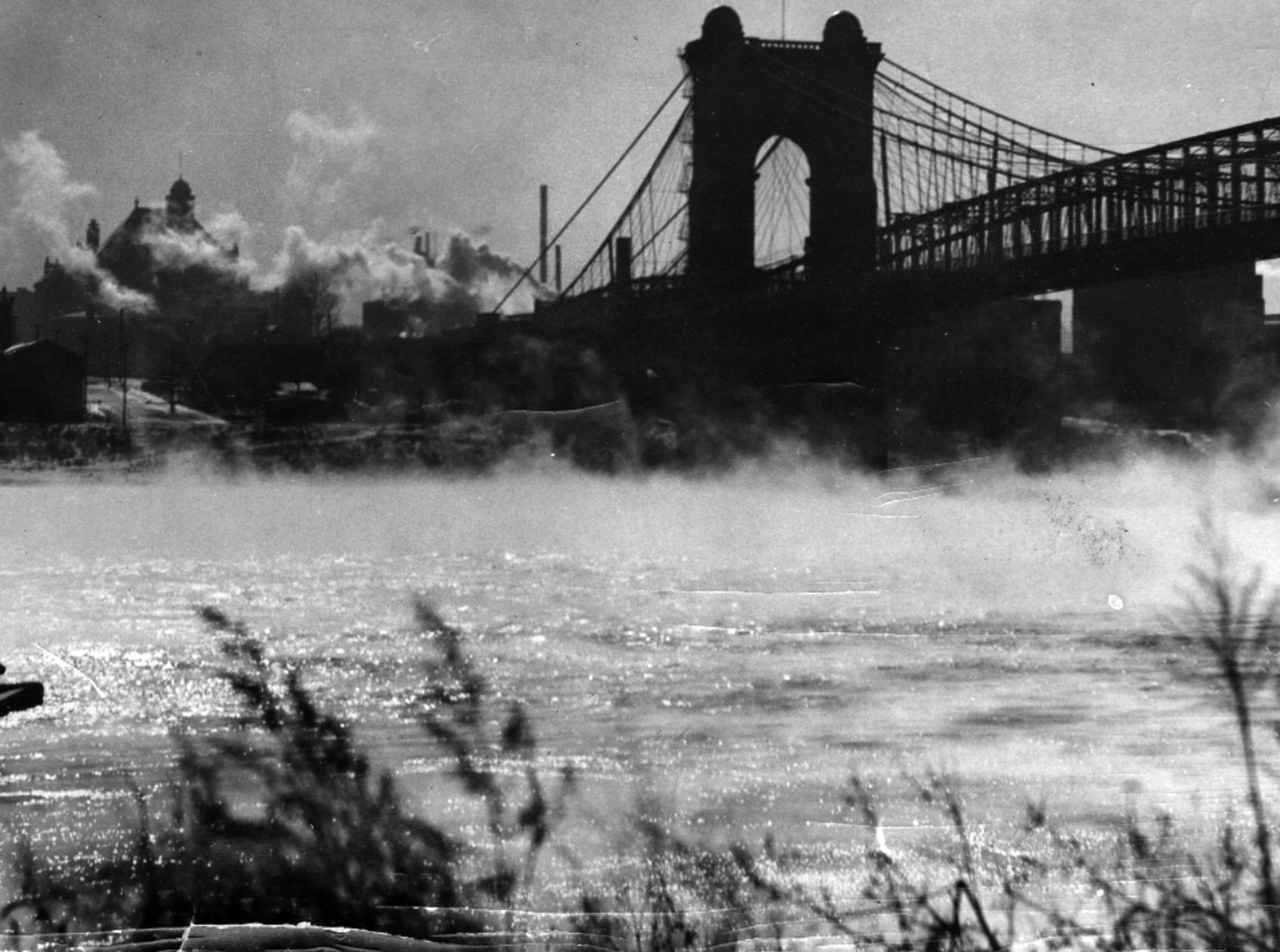 """JANUARY 3, 1975: Still Hanging In There: Like an old, old porch in need of a new floor, the Suspension Bridge connecting downtown Cincinnati and Covington also is worn from much, much traffic. The Kentucky Bureau of Highways will let a contract January 23, 1975 to replace about half the steel grid deck of the bridge, with a completion date of August 1, 1976, and at least one lane to remain open to traffic at all times, tow lanes during peak traffic hours, Countless feet and tires have moved across the structure since The Enquirer on December 2, 1866, noted: """"Yesterday, the greatest work in the country, the Covington and Cincinnati Suspension Bridge was thrown open to the public."""" Headlines above the story said: """"40,000 Foot Passengers On it Yesterday. Freight Cart To Run It During Nighttime."""" Also mentioned was the """"stiffness and rigidity of the structure,"""" which was designed by John Augustus Roebling, who later built the Brooklyn Bridge. The 100th anniversary of the opening of the bridge was observed with proper ceremonies in 1966 at City Hall Square in Covington. Enquirer File Photo scanned December 20, 2010"""