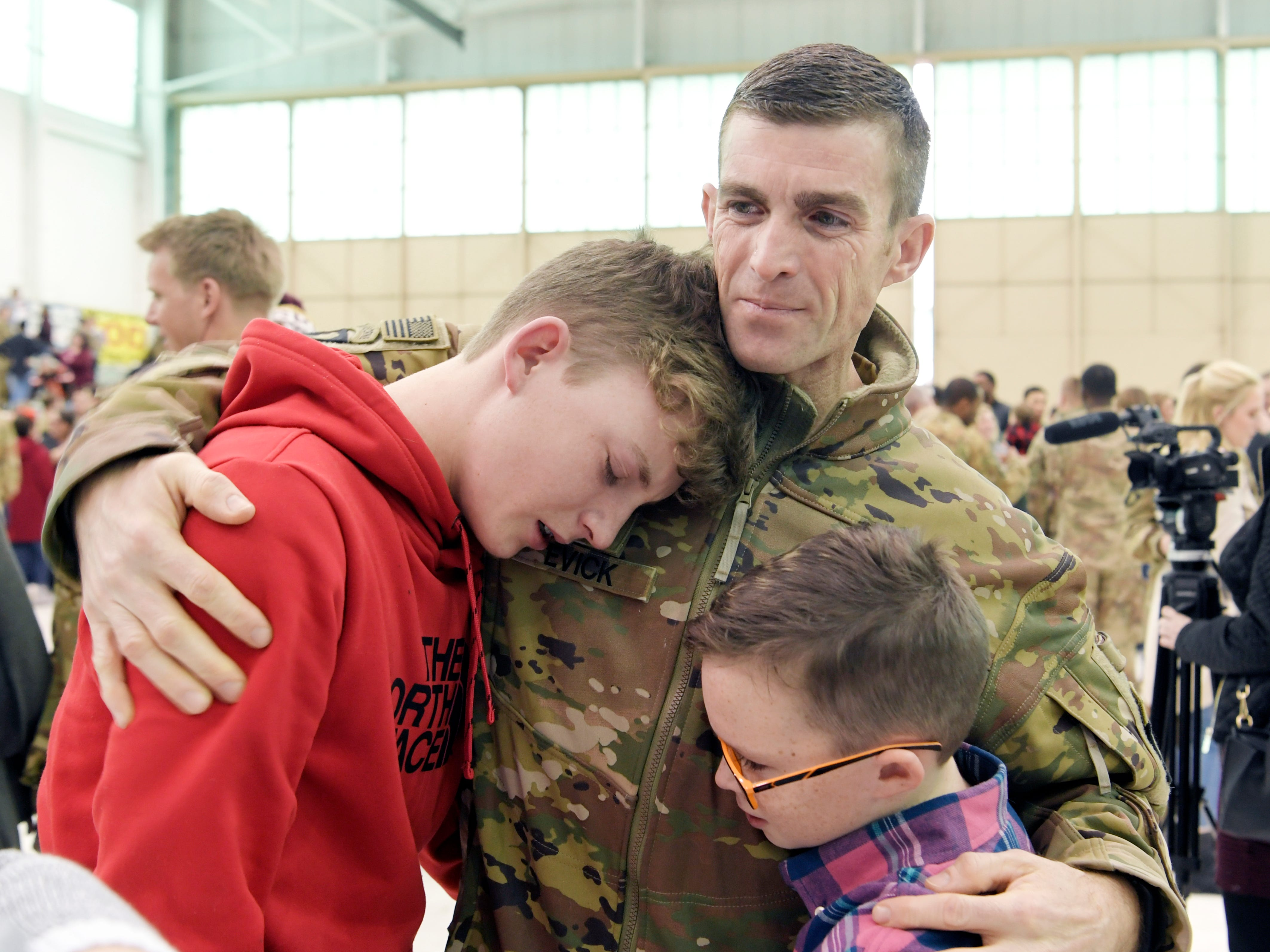 Keagan Evick, 15, and his brother, Trenten, 11, are hugged by their father, Kurtis Evick, during a welcome home ceremony for 171 soldiers from 101st Combat Aviation Brigade, 101st Airborne Division (Air Assault) which returned to Fort Campbell, KY on Friday, Feb. 15, 2019 after a nine-month deployment to Afghanistan.
