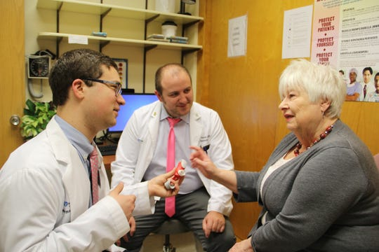 (Left to right)Andrew Giaquinto, pharmacy resident and Michael Casias, clinical pharmacist/assistant professor, Hunterdon Healthcare, provide education on using an inhaler during an office visit with June Prince of Riegelsville, Pa.