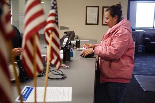 "Jessica Bensley, who had her ballot rejected in the November election after wrongly being listed as a felon, receives her ""I Voted"" sticker after casting her ballot on Friday, Feb. 15, 2019, in Des Moines."