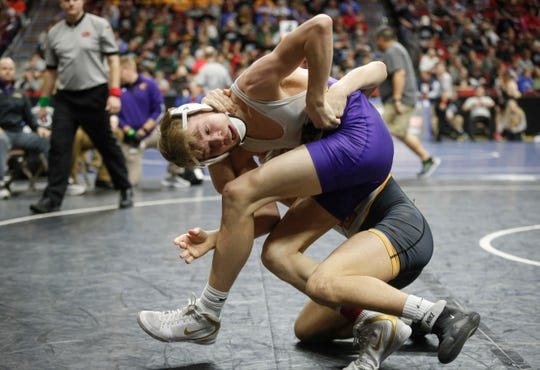 Johnston junior Thomas Edwards works to break free from Southeast Polk freshman Joel Jesuroga at 120 pounds during the state wrestling quarterfinals on Friday, Feb. 15, 2019, at Wells Fargo Arena in Des Moines.