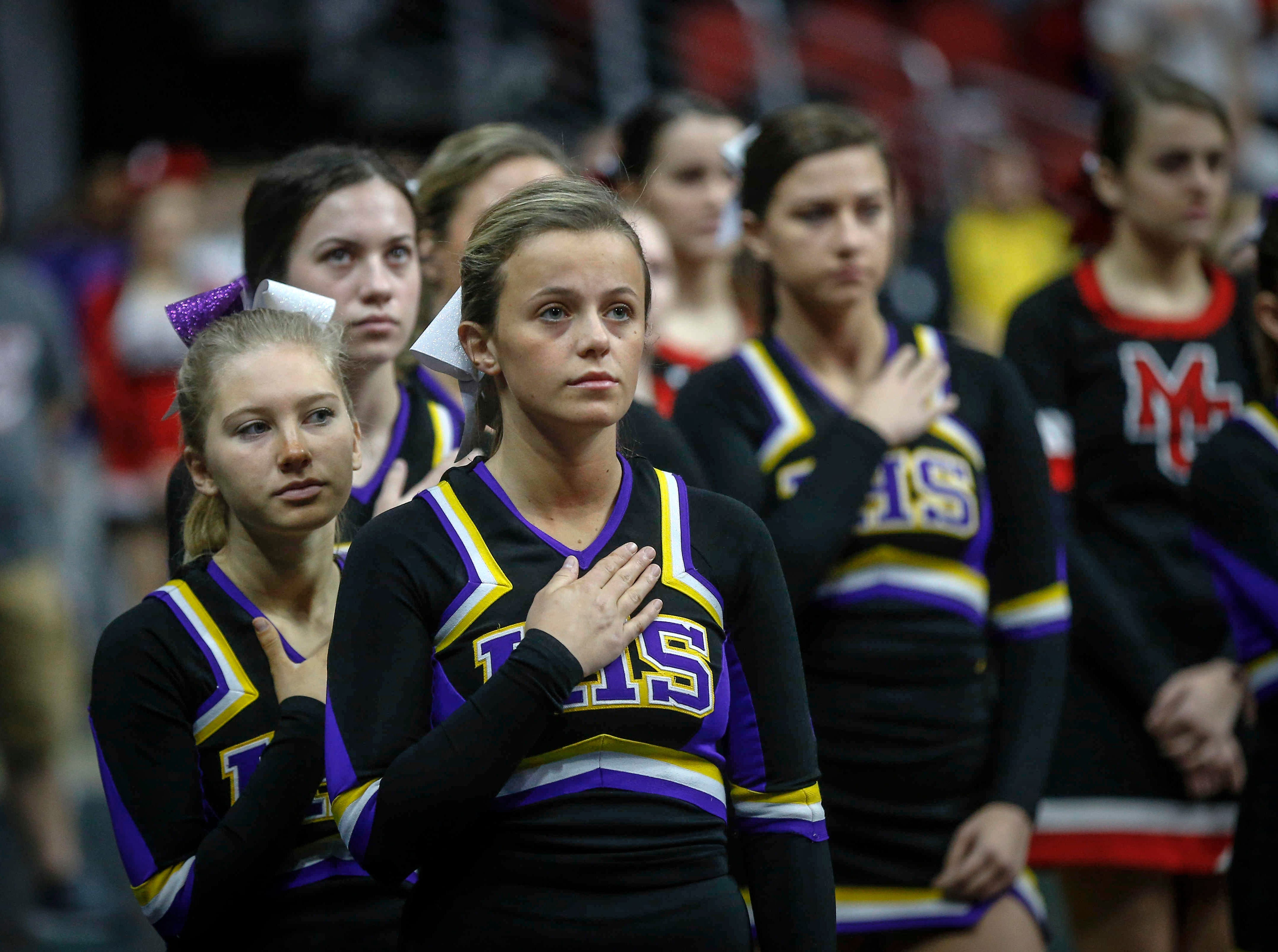 The Indianola cheerleaders observe the National Anthem prior to the start of the state wrestling quarterfinals on Friday, Feb. 15, 2019, at Wells Fargo Arena in Des Moines.