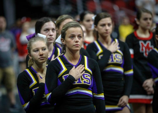 The Indianola cheerleaders observe the national anthem prior to the start of the state wrestling quarterfinals Friday at Wells Fargo Arena in Des Moines.