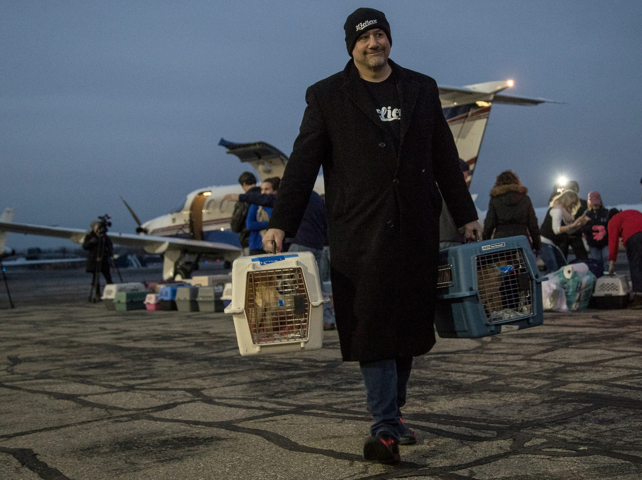 Harry Berberian of Southfield carries two crates of rescue dogs off the plane at Willow Run Airport in Ypsilanti Township, Thursday, Feb. 14, 2019. Around 91 rescue dogs flew in from Fresno, Calif. to get adopted at one of the metro Detroit Michigan Humane Society facilities.