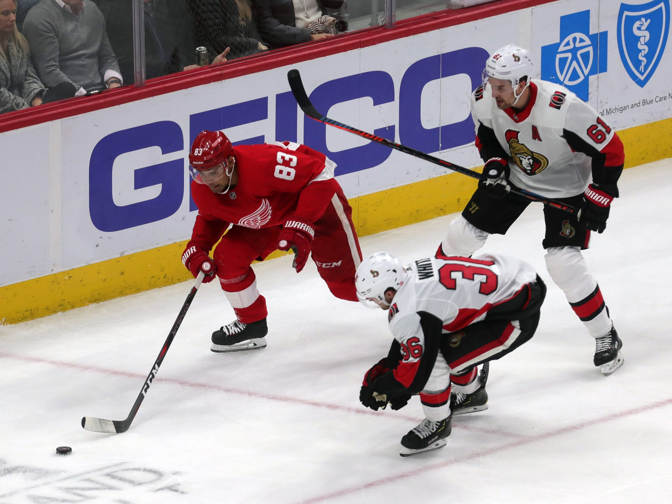 Red Wings defenseman Trevor Daley goes for the puck against Ottawa Senators center Colin White and right wing Mark Stone during second period action on Feb. 14, 2019 at Little Caesars Arena.
