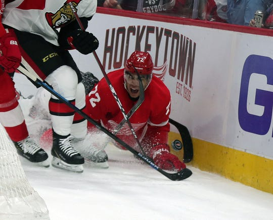 Red Wings center Andreas Athanasiou is checked by Ottawa Senators defenseman Christian Jaros on Feb. 14, 2019 at Little Caesars Arena in Detroit.