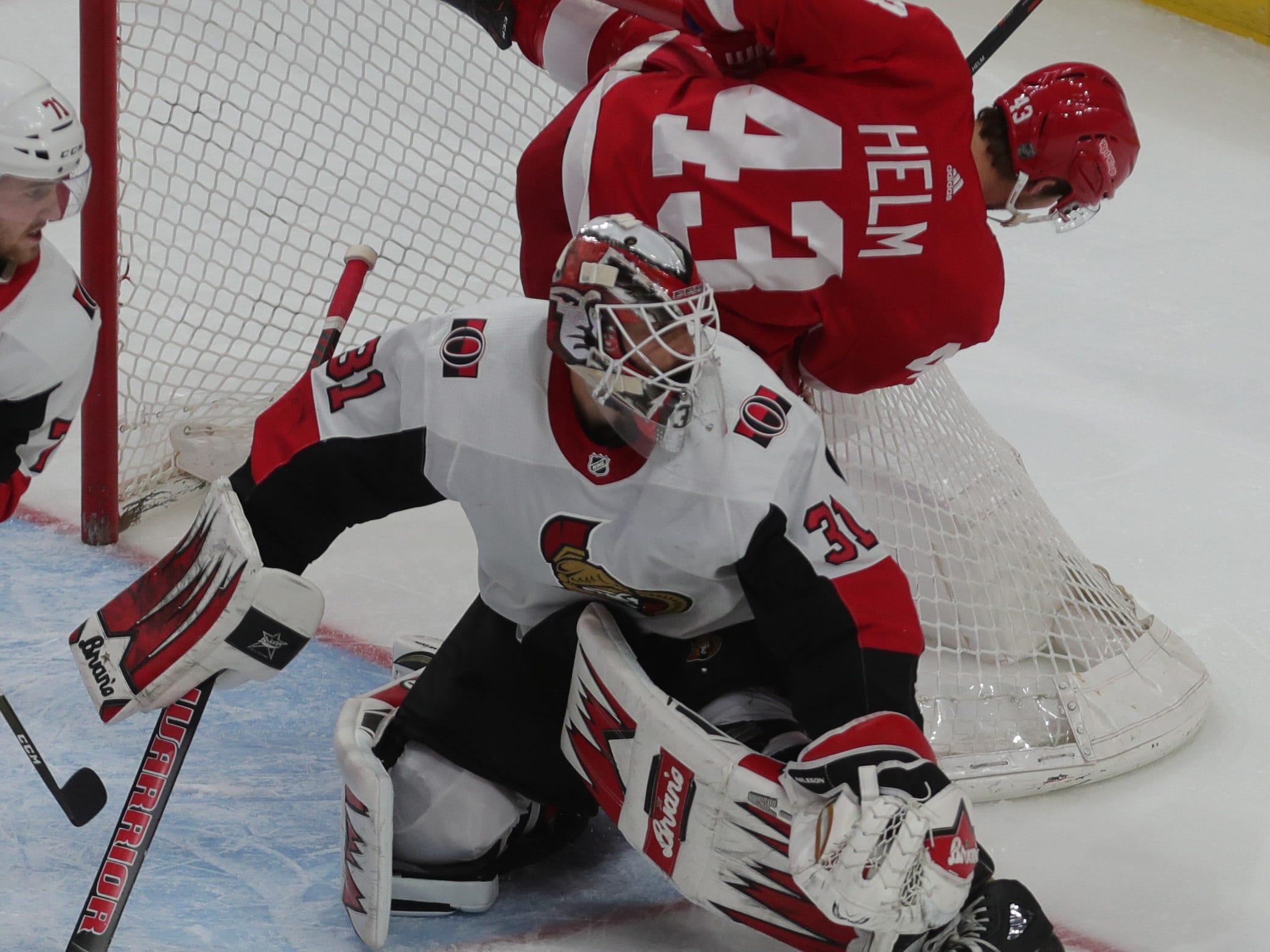 Red Wings forward Darren Helm is checked into Ottawa Senators goalie Anders Nilsson on Thursday in Detroit.