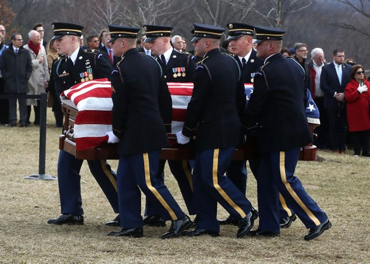 A military honor guard carries the casket of former Rep. John Dingell during a funeral service at Arlington National Cemetery Friday in Arlington, Va.