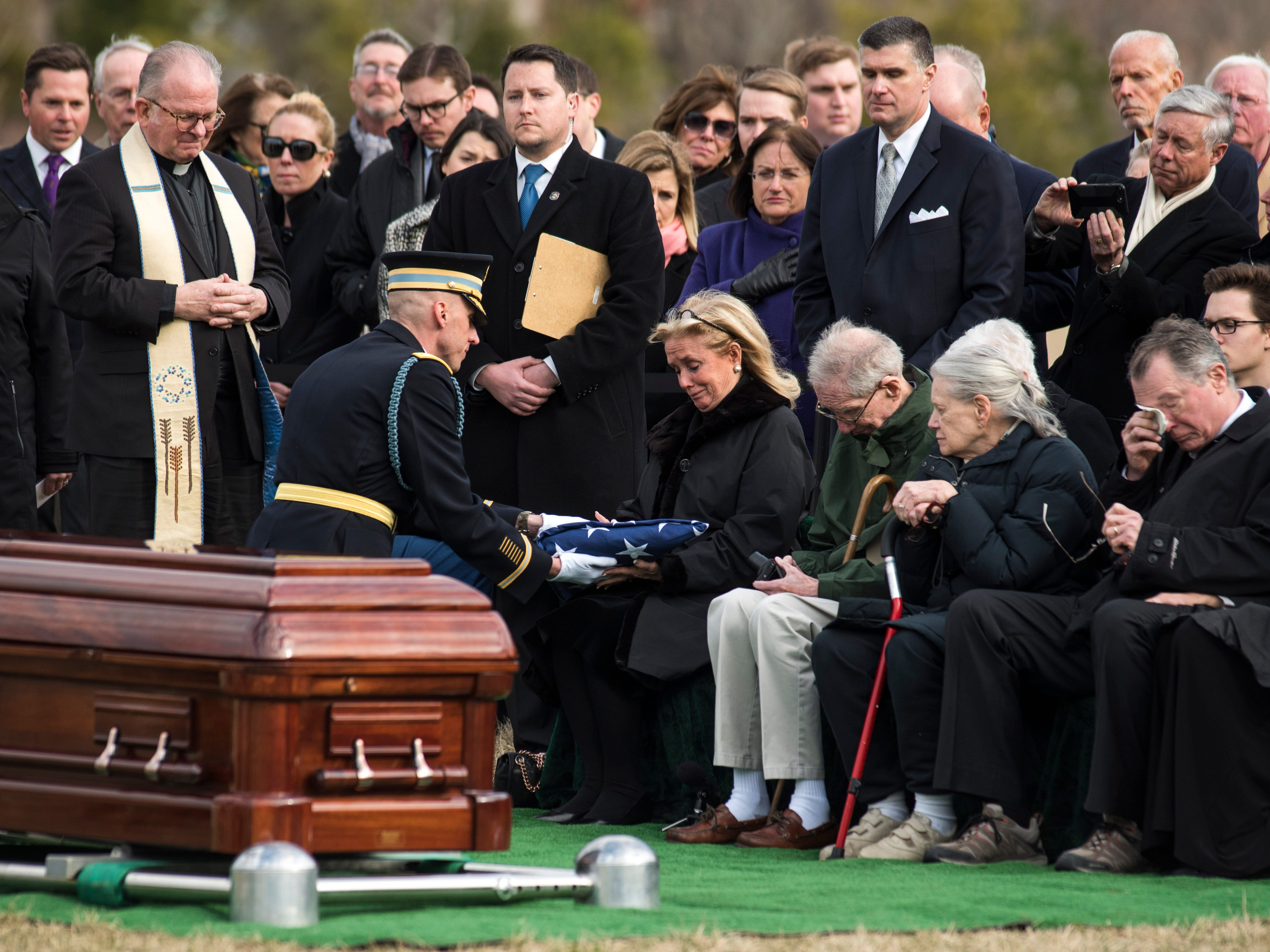 Lt. Col. Allen Kehoe presents the flag from the casket of former Rep. John Dingell, D-Mich., to his wife, Rep. Debbie Dingell, D-Mich., during burial services at Arlington National Cemetery on Friday, Feb. 15, 2019 in Arlington, Va.