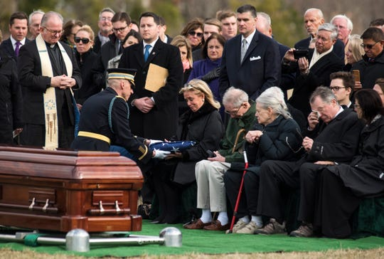 Army Lt. Col. Allen Kehoe of the Old Guard presents the flag from the casket of former Rep. John Dingell, D-Mich., to his wife, Rep. Debbie Dingell, D-Mich., during burial services at Arlington National Cemetery on Friday, Feb. 15, 2019 in Arlington, Va. To Debbie Dingell's right are John Dingell's younger siblings, Jim Dingell and Jule Walowac, and his son Christopher Dingell.