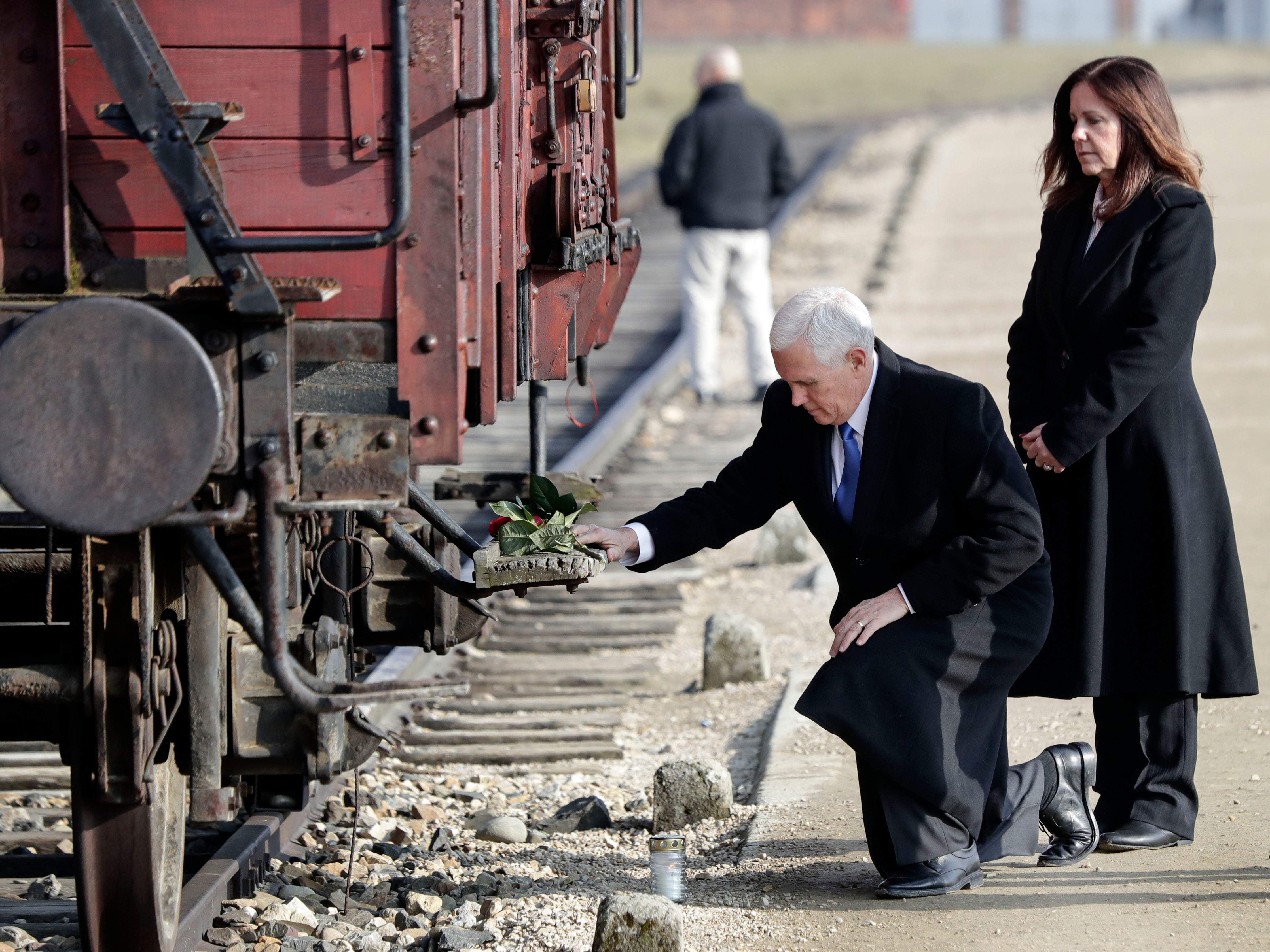 United States Vice President Mike Pence kneels beside his wife Karen, right, at a historic freight car during their visit to the former Nazi concentration camp Auschwitz-Birkenau in Oswiecim, Poland, Friday, Feb. 15, 2019. The freight car was used to transport Jews to the death camp.