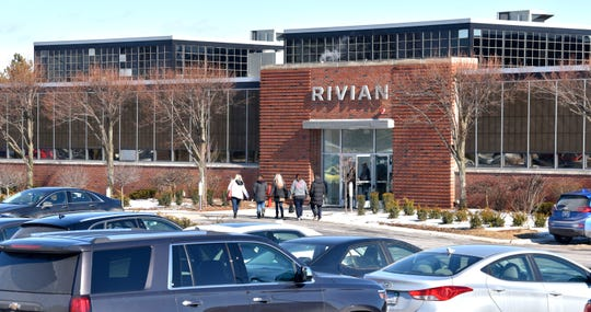 Employees approach the front entrance of electric truck start-up Rivian Automotive's engineering center in Plymouth. Rivian is getting a $700-million cash injection led by Amazon.com Inc. to build their vehicles in Normal, Illinois.