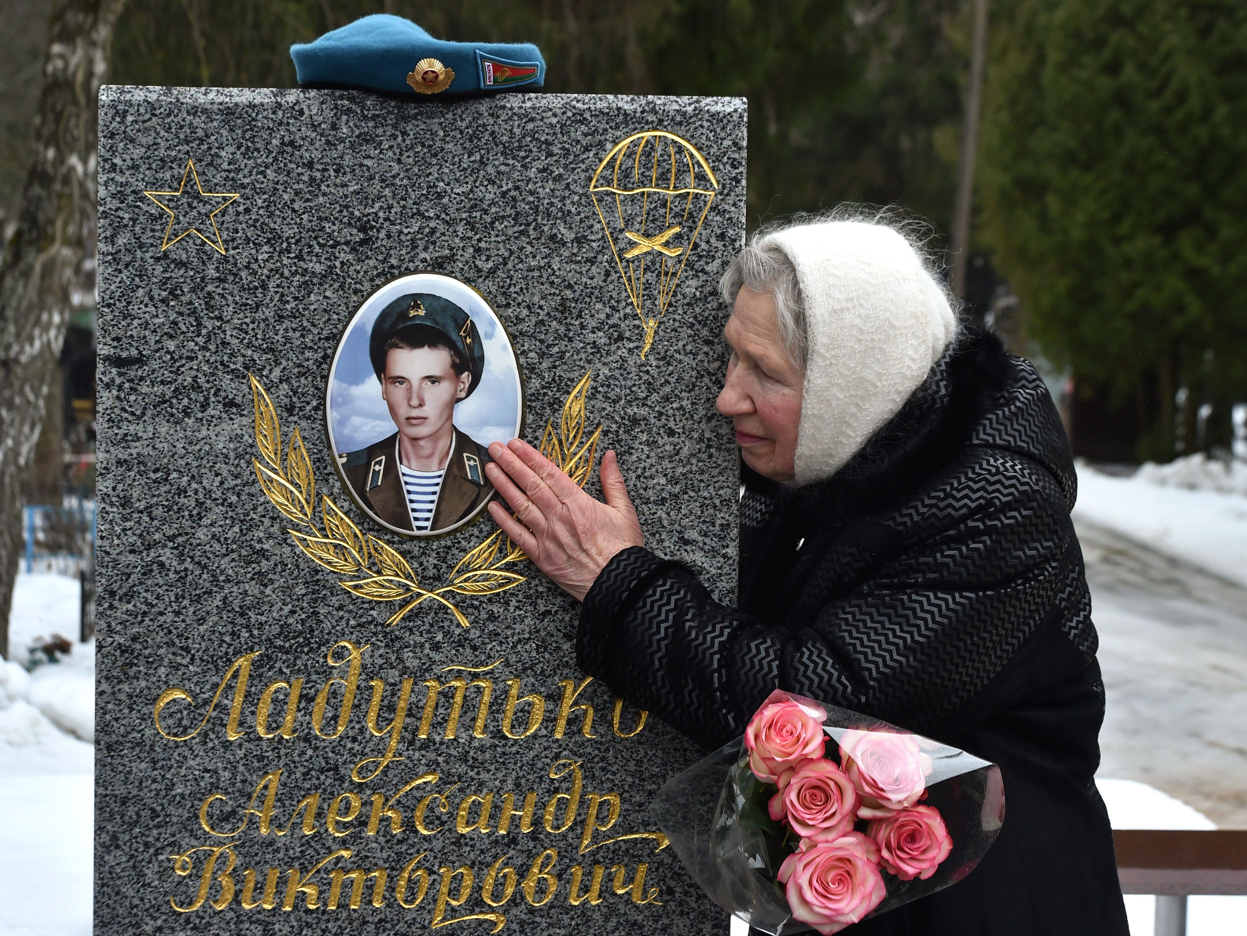 Larisa Ladutko, 78, visits a grave of her son Alexander, killed in 1984 during the Soviet War in Afghanistan on the 30th anniversary of the Soviet troops withdrawal at Chizhovskoe cemetery, outside Minsk on Feb. 15, 2019.