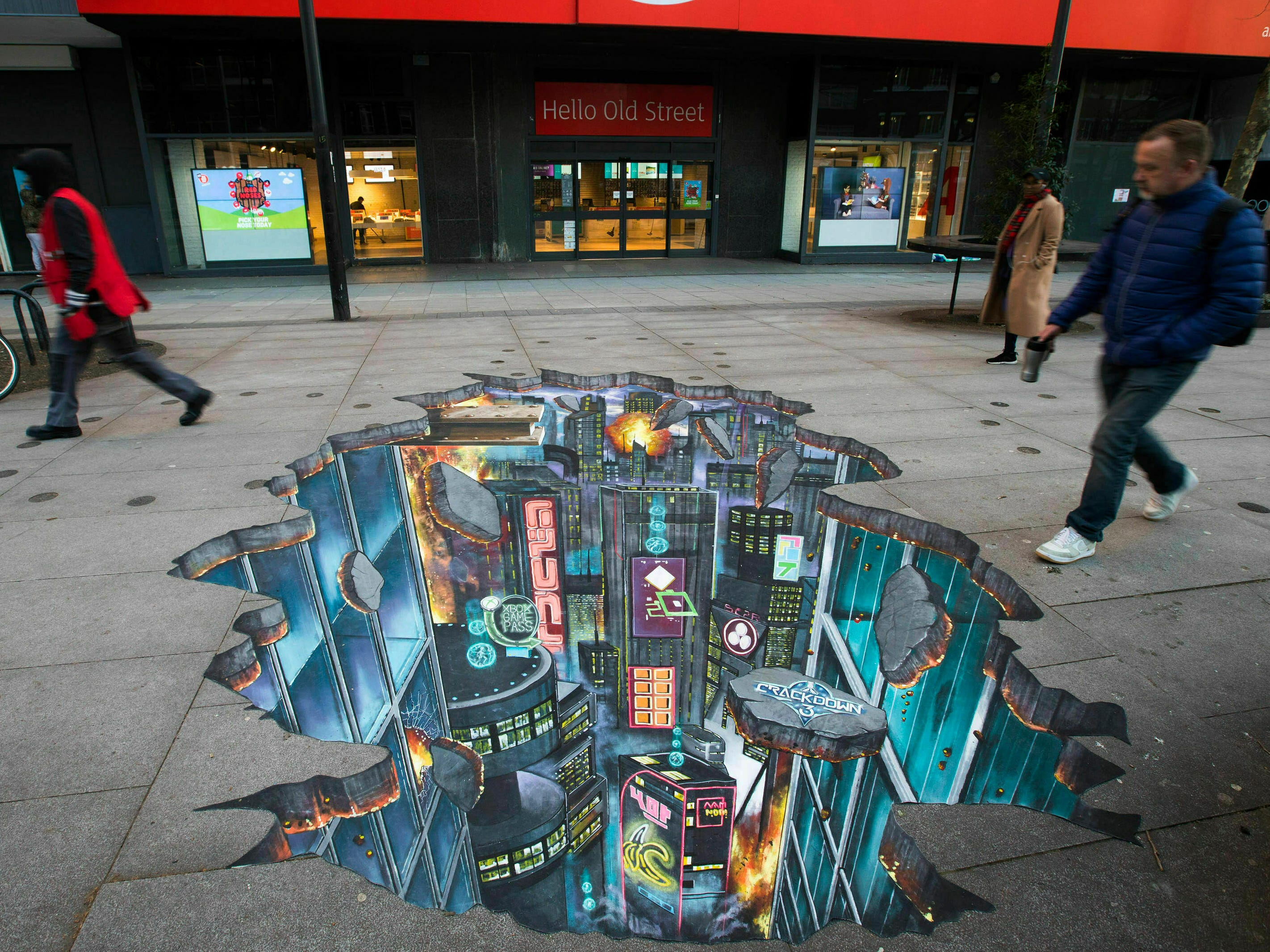 Pedestrians pass by a 3D street artwork outside Argos in London depicting a subterranean world under the pavement, created by 3D Joe & Max to celebrate the release of Crackdown 3 on Xbox, Friday Feb. 15, 2019. The artists have designed the piece to reflect a 'Portal to Pacific City', as featured in the game.