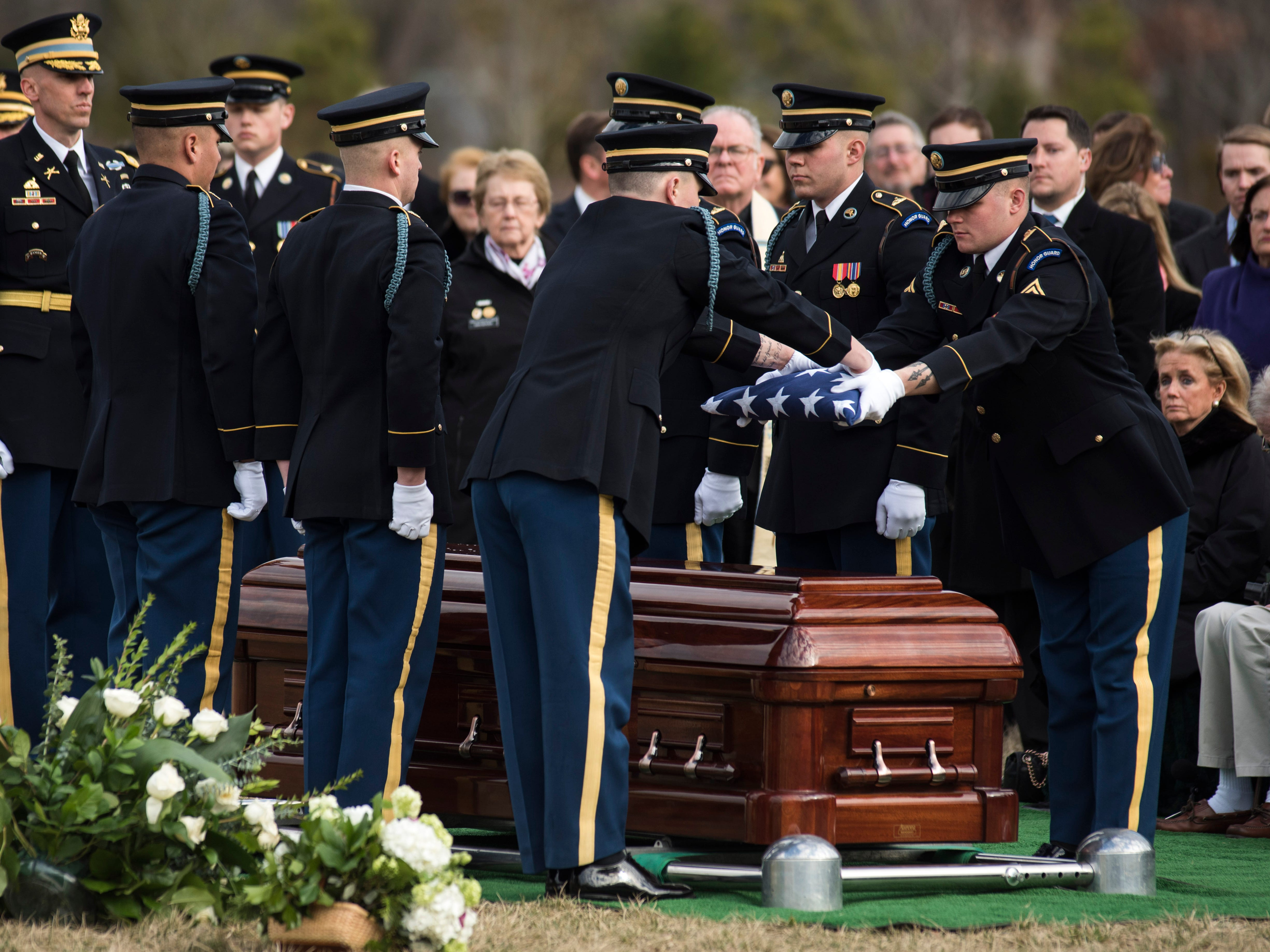 Honor guard members fold the flag above the casket of former Rep. John Dingell, D-Mich. during burial services at Arlington National Cemetery on Friday, Feb. 15, 2019 in Arlington, Va. At right is Rep. Debbie Dingell, D-Mich., the wife of John Dingell.