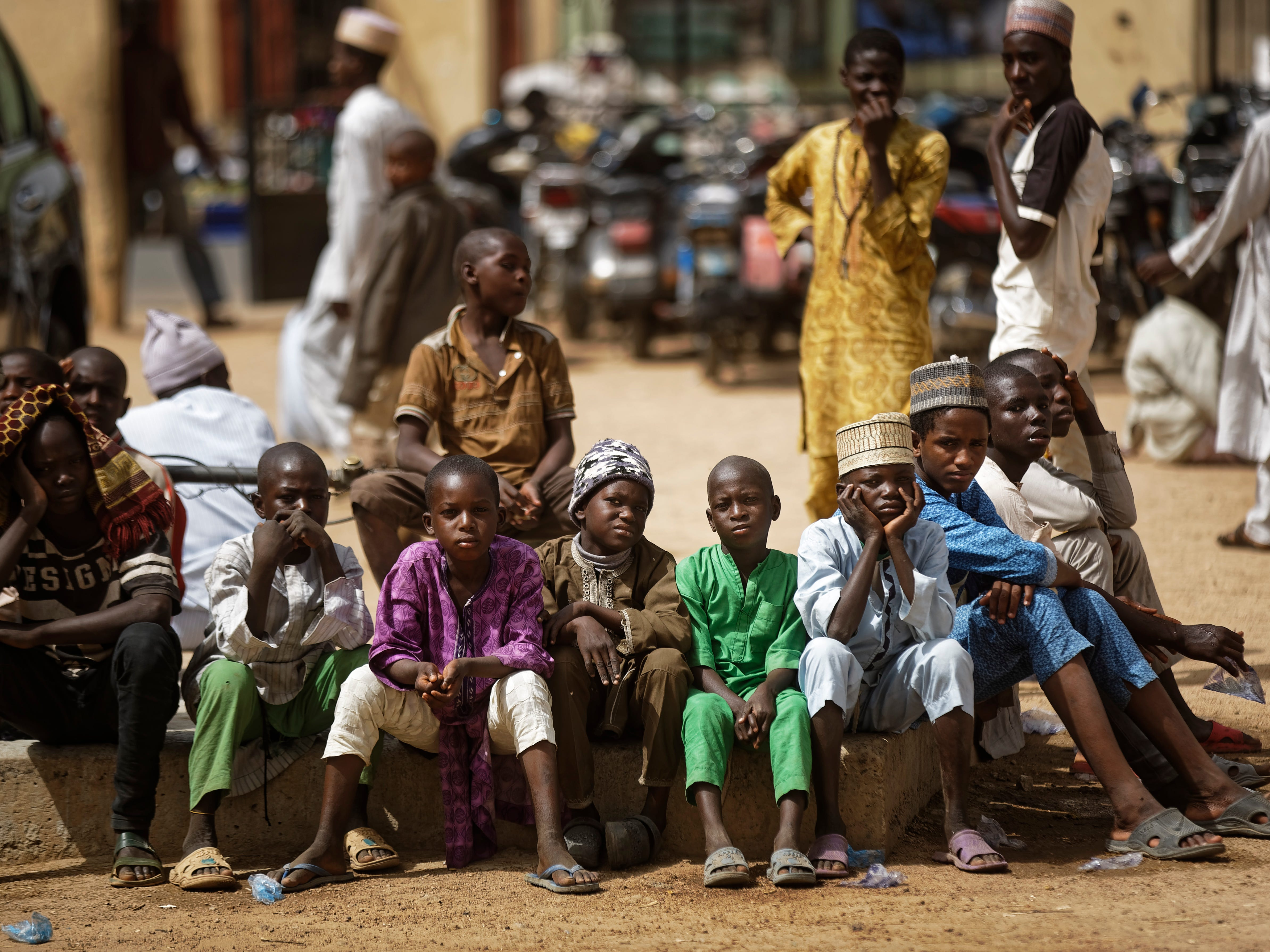 Young Muslim boys wait for traditional Friday prayers to begin at a mosque near to the Emir's palace a day prior to the start of the elections, in Kano, northern Nigeria, Friday, Feb. 15, 2019. Nigeria is due to hold general elections on Saturday, pitting incumbent President Muhammadu Buhari against leading opposition presidential candidate Atiku Abubakar.