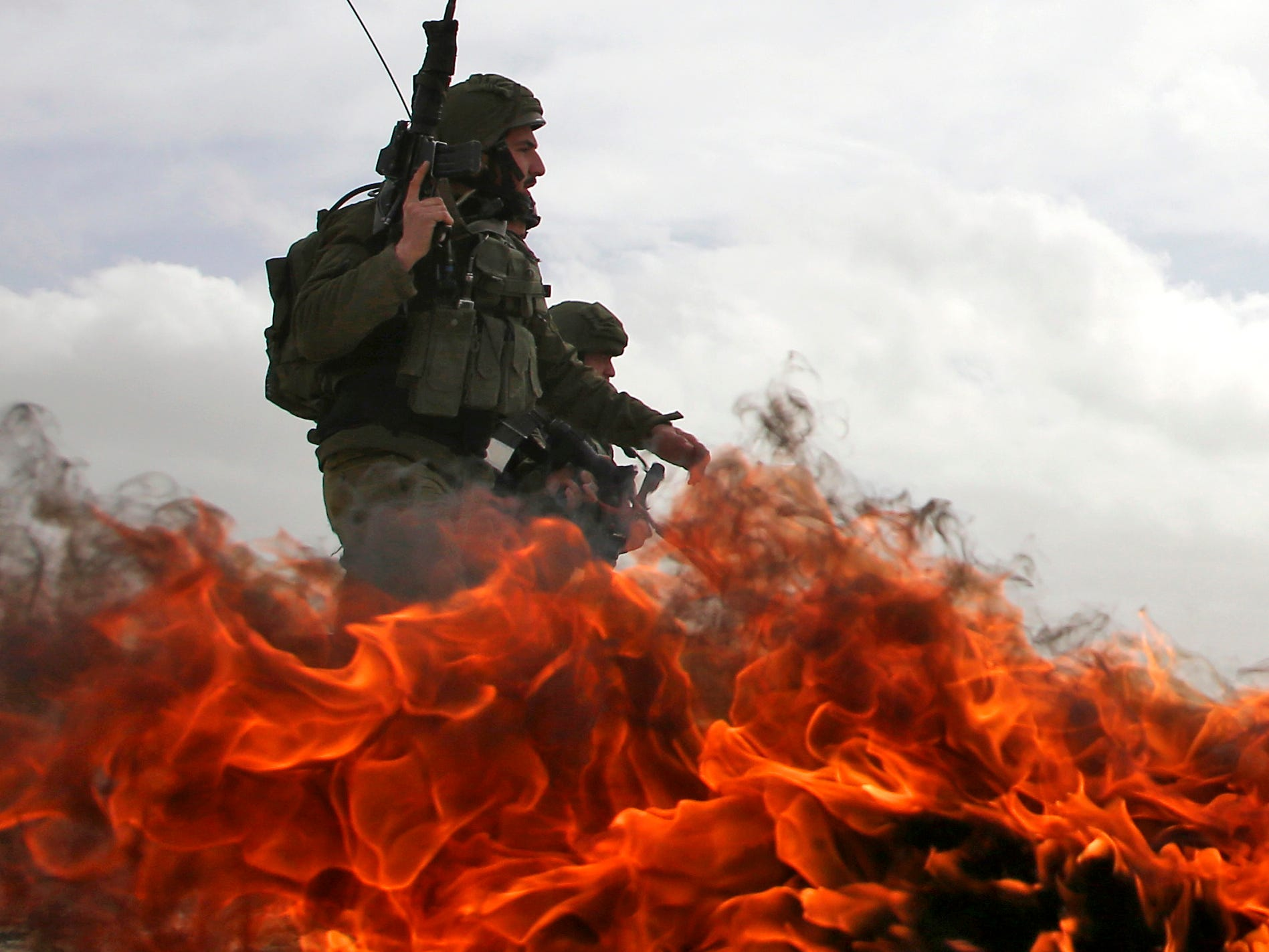 Israeli soldiers walk past burning tires during clashes with Palestinian protestors following a demonstration against Jewish settlements in the West Bank village of Urif, south of Nablus, on Feb. 15, 2019.