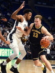 Michigan forward Ignas Brazdeikis dribbles around Penn State forward Lamar Stevens during the first half on Tuesday night.