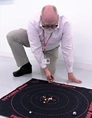 Troy Smythe, education and interpretation supervisor at the Corning Museum of Glass, demonstrates a popular game of marbles. The museum will host a special family event Sunday focusing on glass marbles.