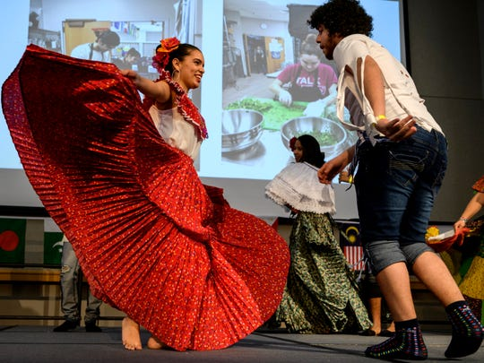 Kaelyn Moreno, left,  performs a dance with Joha DeGracia, right, and other University of Southern Indiana students from Panama during the International Food Expo held in USI's Carter Hall in Evansville, Ind., Friday, Feb. 15, 2019. Students in the International Club prepared food from around the world to serve to attendees while also providing entertainment through dances, musical performances and a fashion show.
