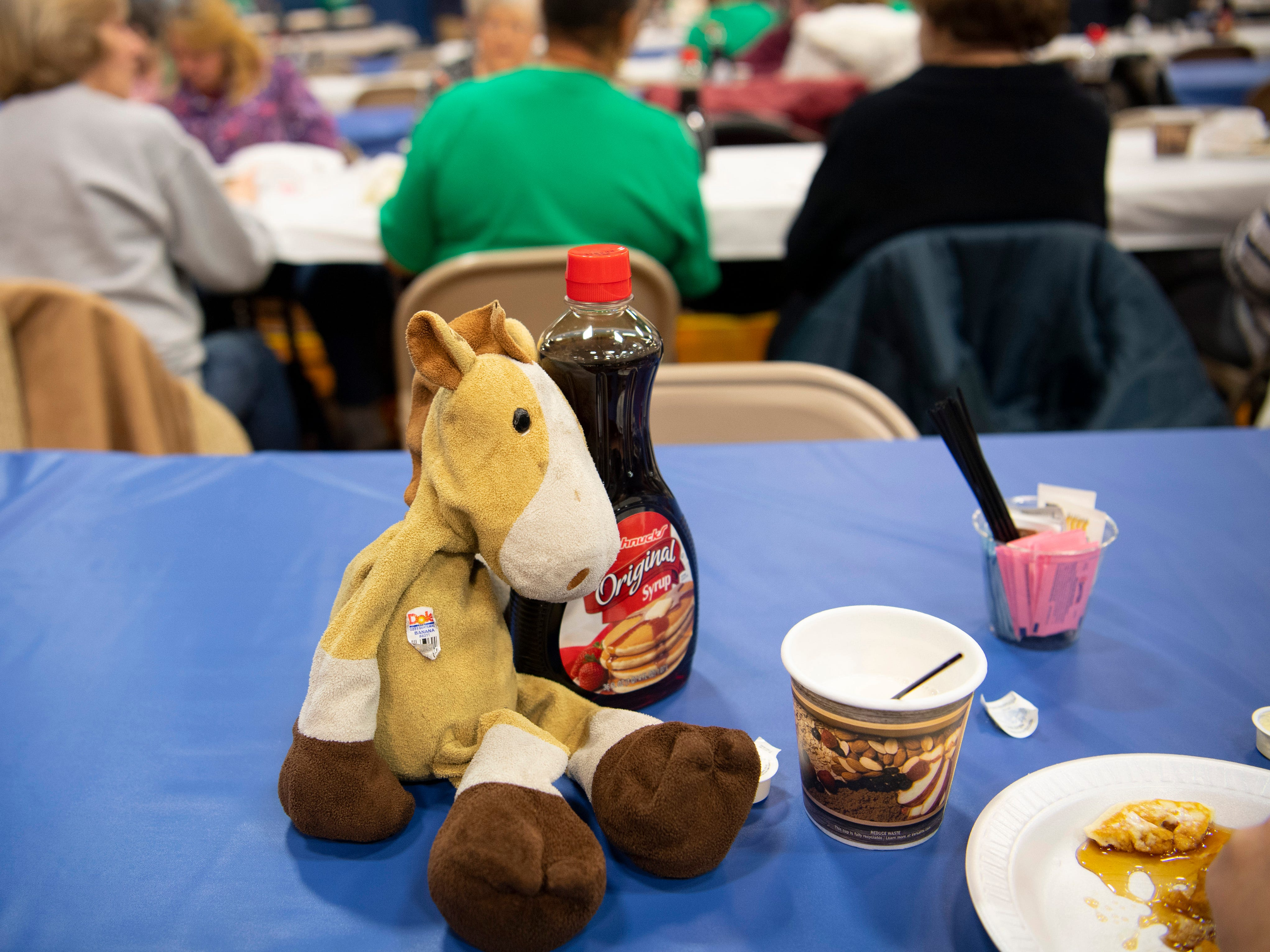 Mr. Horse, Ethan Vaupel's travel companion, kills time with a bottle of syrup as his 7-year-old buddy finishes his pancakes at the 31st Annual Pancake Days at the Downtown YMCA Friday morning. The pancakes, sausage, milk, coffee and orange juice will be served up again Saturday from 6 a.m. to 1 p.m. and Sunday from 8 a.m. to 1 p.m.