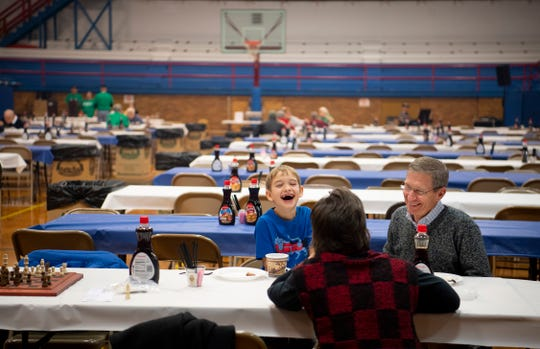 Elliott Piekos, 8, and his grandparents, John and Donna Gross, fit in their pancakes and sausage between chess games at the 31st Annual Pancake Days at the Downtown YMCA Friday morning. The pancakes, sausage, milk, coffee and orange juice will be served up again Saturday from 6 a.m. to 1 p.m. and Sunday from 8 a.m. to 1 p.m.