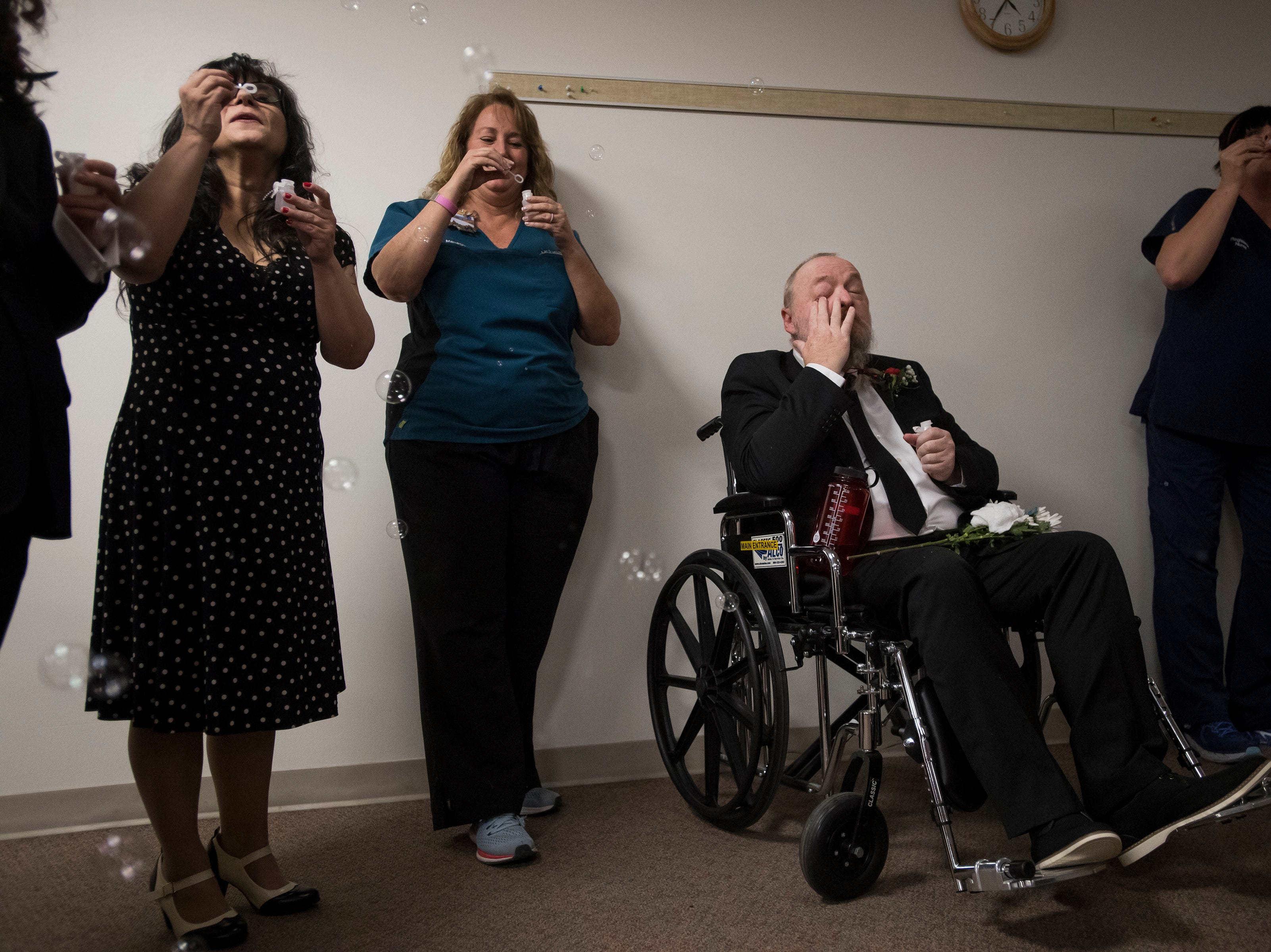 Father of the bride Paul Justice tears after his daughter and son-in-law Grace and James Christian walk past before their wedding reception on Thursday, Feb. 14, 2019, at UCHealth Poudre Valley Hospital in Fort Collins, Colo.