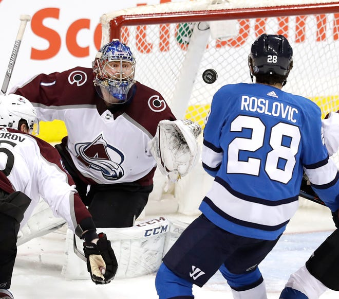 Colorado Avalanche goaltender Semyon Varlamov watches a shot by Winnipeg's Jack Roslovic during a game Thursday night in Winnipeg, Manitoba. The Avalanche will return home to the Pepsi Center in Denver for a 1 p.m. game Saturday against the St. Louis Blues.