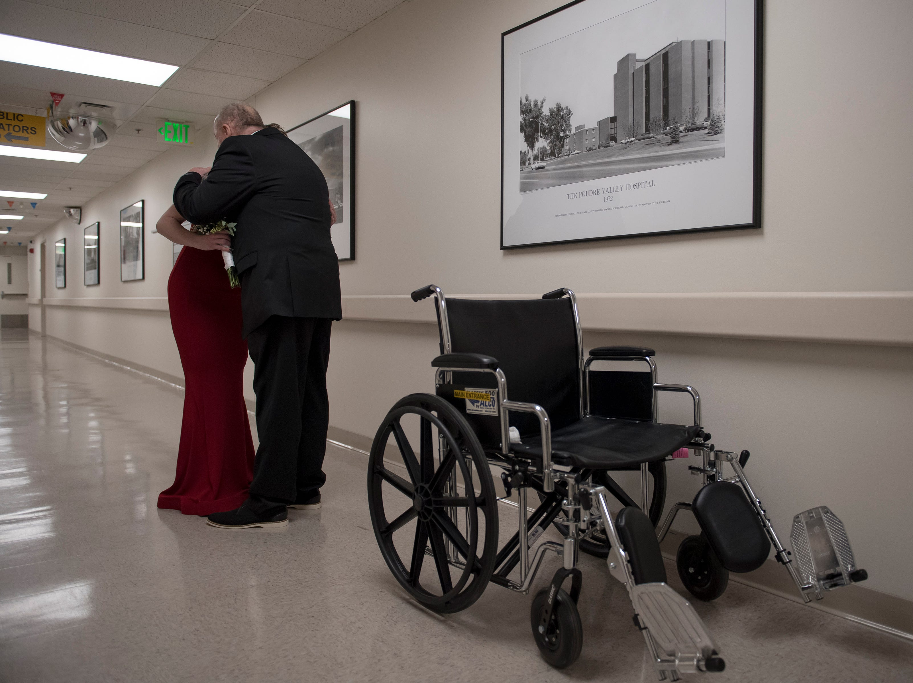 Father of the bride Paul Justice hugs his daughter Grace Justice before walking her down the hallway to the chapel on Thursday, Feb. 14, 2019, at UCHealth Poudre Valley Hospital in Fort Collins, Colo.