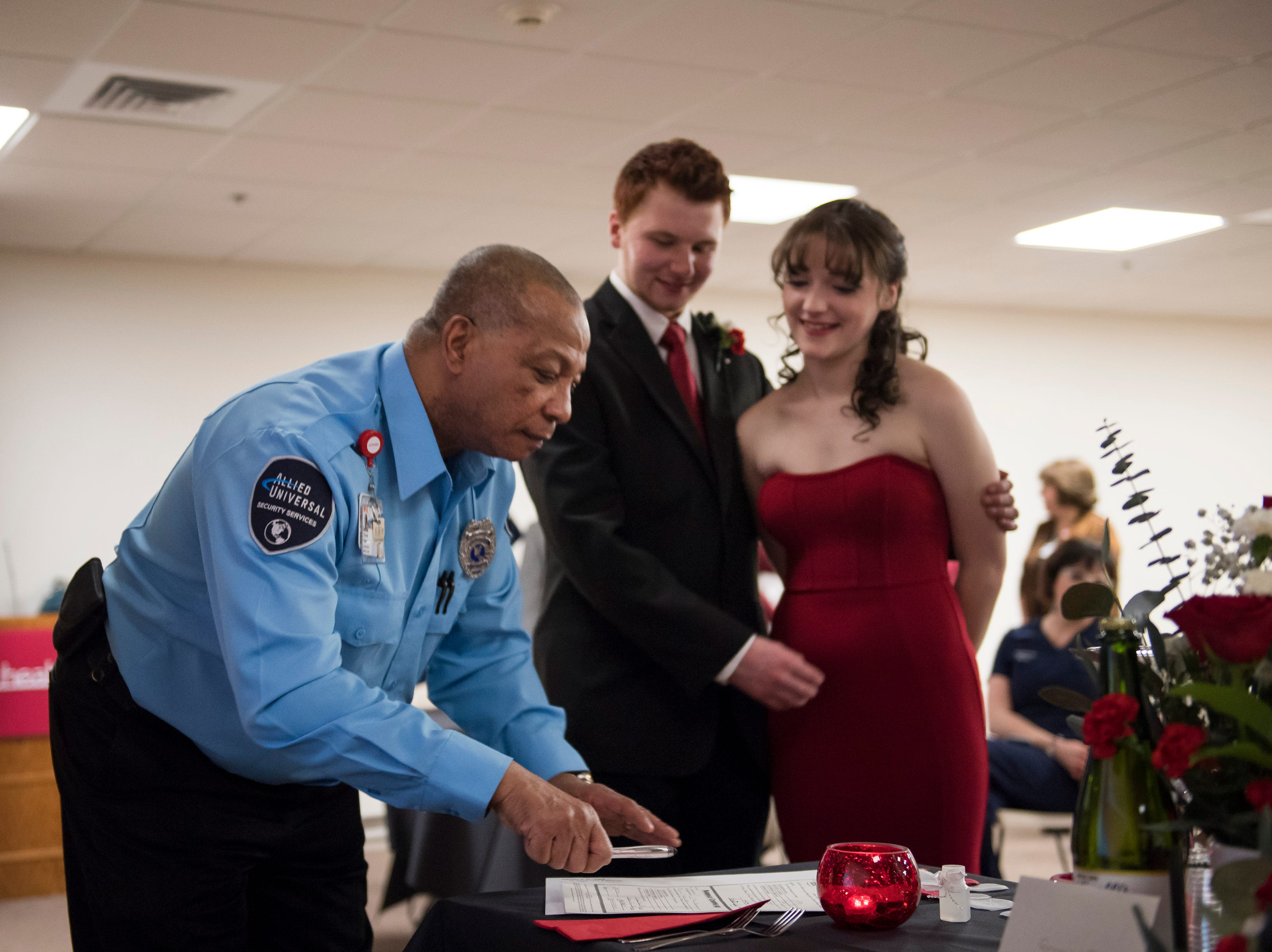 Security officer Tyrone Payne signs the marriage license as a witness for newlyweds James and Grace Christian on Thursday, Feb. 14, 2019, at UCHealth Poudre Valley Hospital in Fort Collins, Colo.