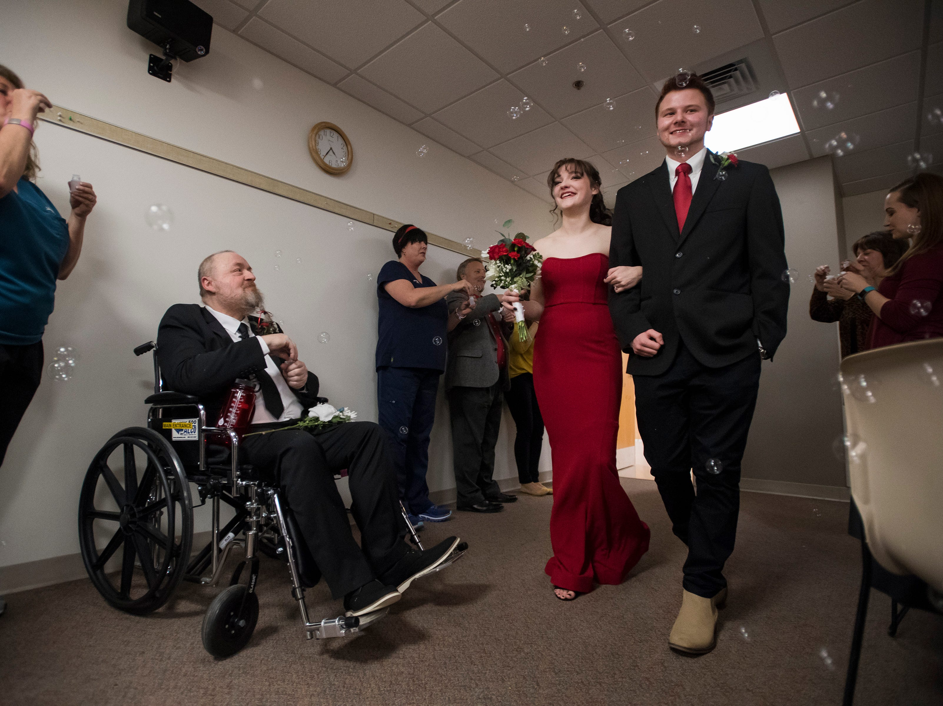 Newlyweds James and Grace Christian Walk into the venue for their reception past UCHealth employees and family members blowing bubbles and Grace's father Paul Justice, left, on Thursday, Feb. 14, 2019, at UCHealth Poudre Valley Hospital in Fort Collins, Colo.
