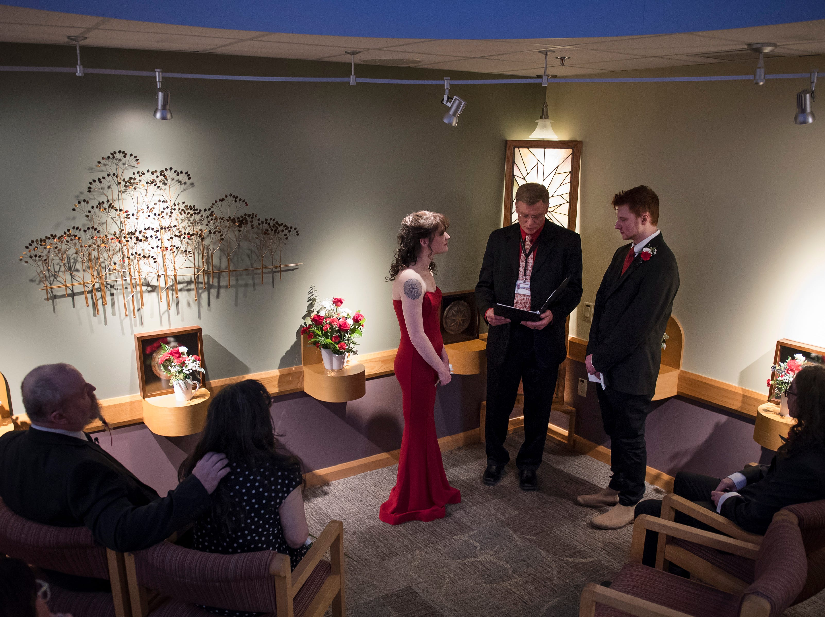 """Chaplain Terry Skov conducts the wedding ceremony of Grace Justice and James """"Christian"""" Christian while Grace's father and mother, Paul and Kelly Justice, left, and brother Dean Justice, right, look on, on Thursday, Feb. 14, 2019, at UCHealth Poudre Valley Hospital in Fort Collins, Colo."""