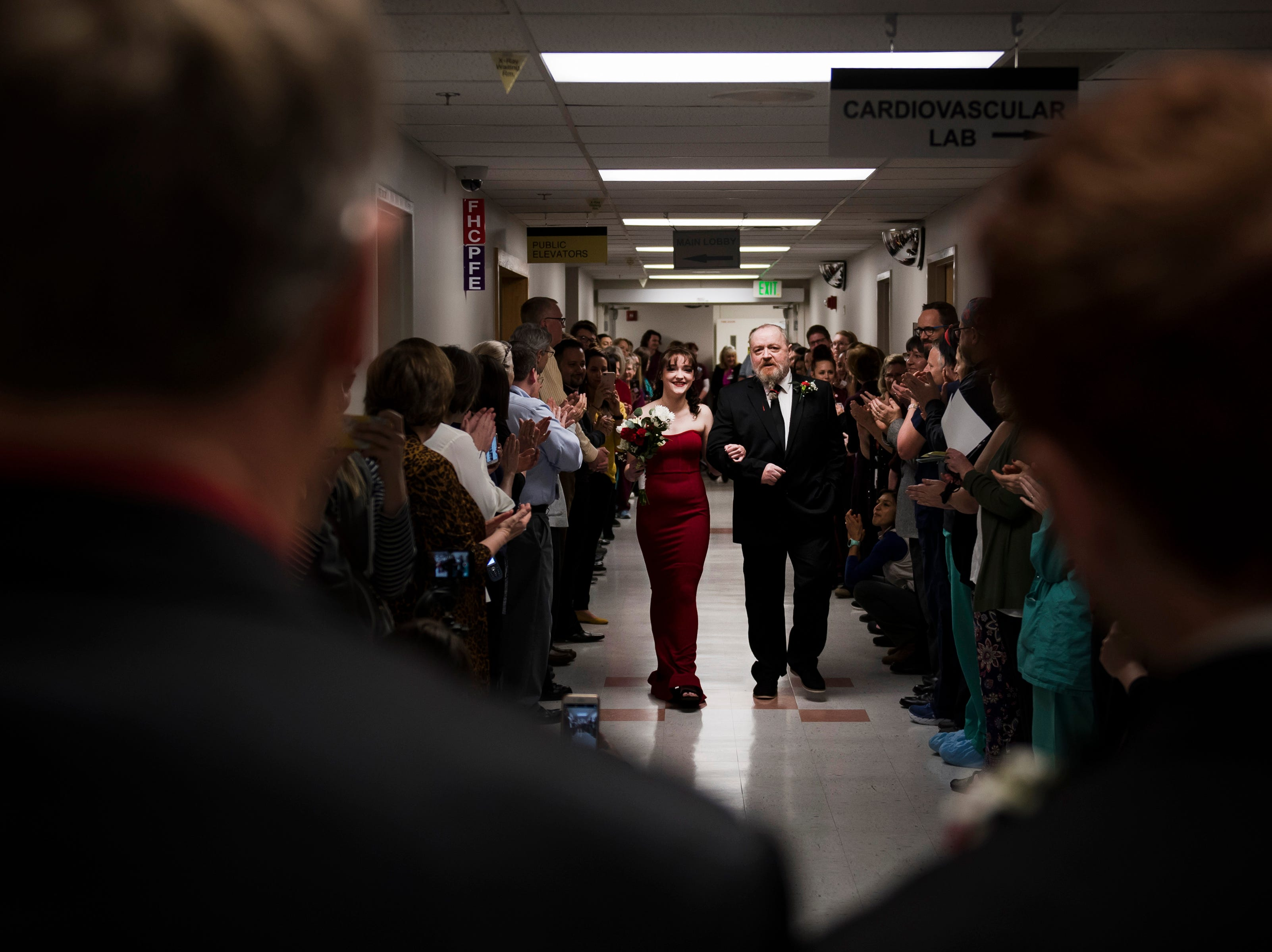 Father of the bride Paul Justice walks how daughter Grace Justice down the hallway leading to the chapel lined with UCHealth employees during Grace's wedding to finance James Christian on Thursday, Feb. 14, 2019, at UCHealth Poudre Valley Hospital in Fort Collins, Colo.