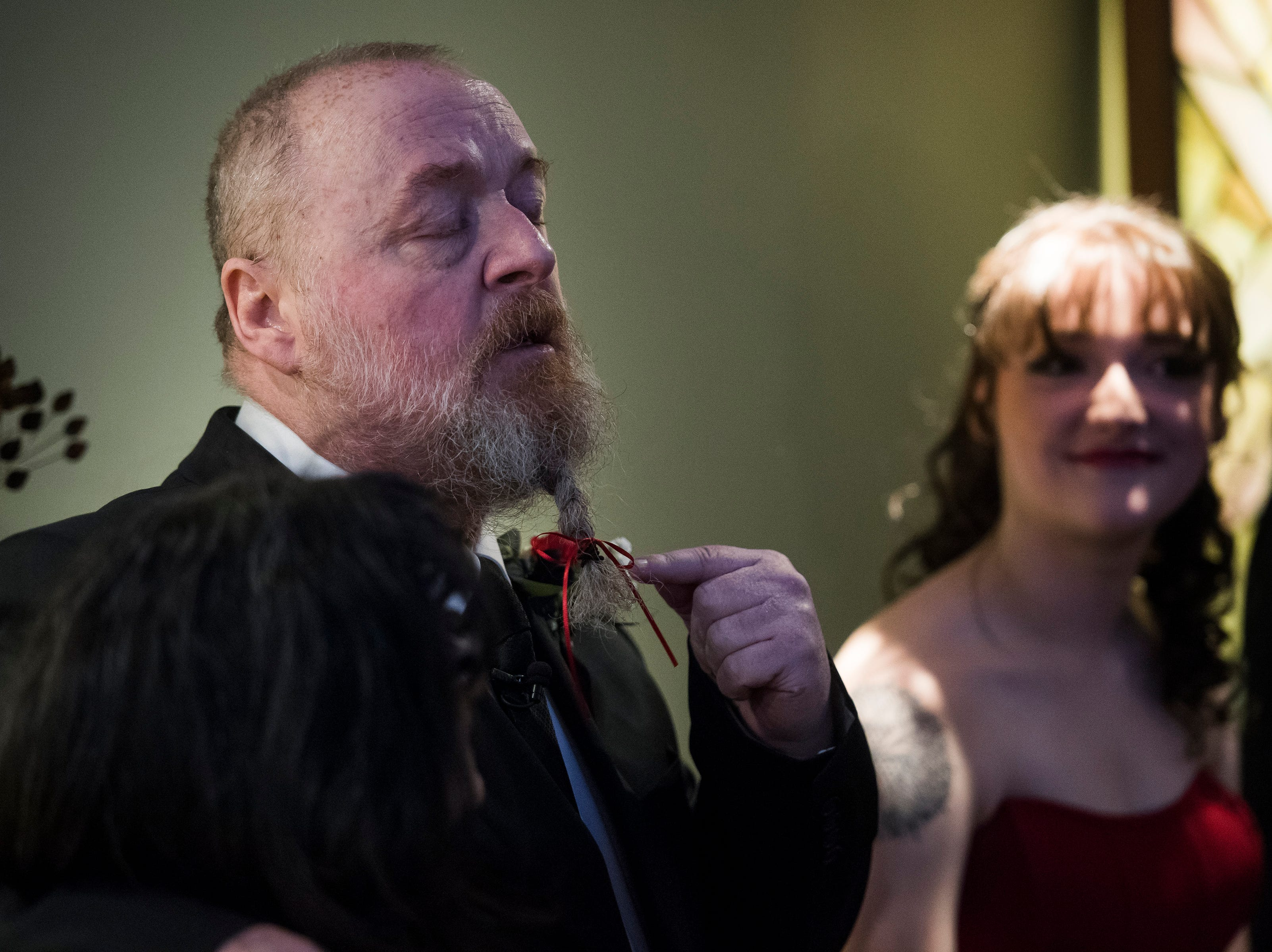 Father of the bride Paul Justice gives speech and points out his beard, braided by his daughter, at the beginning of Grace Justice and James Christian's wedding on Thursday, Feb. 14, 2019, at UCHealth Poudre Valley Hospital in Fort Collins, Colo.