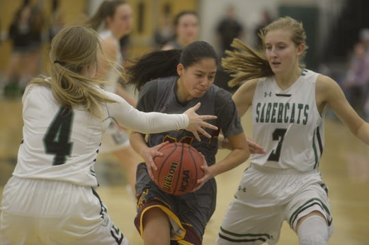 Rocky Mountain basketball player Laisha Armendariz Lopez tries to work past Fossil Ridge defenders during a game earlier this month. The SaberCats won 66-39.