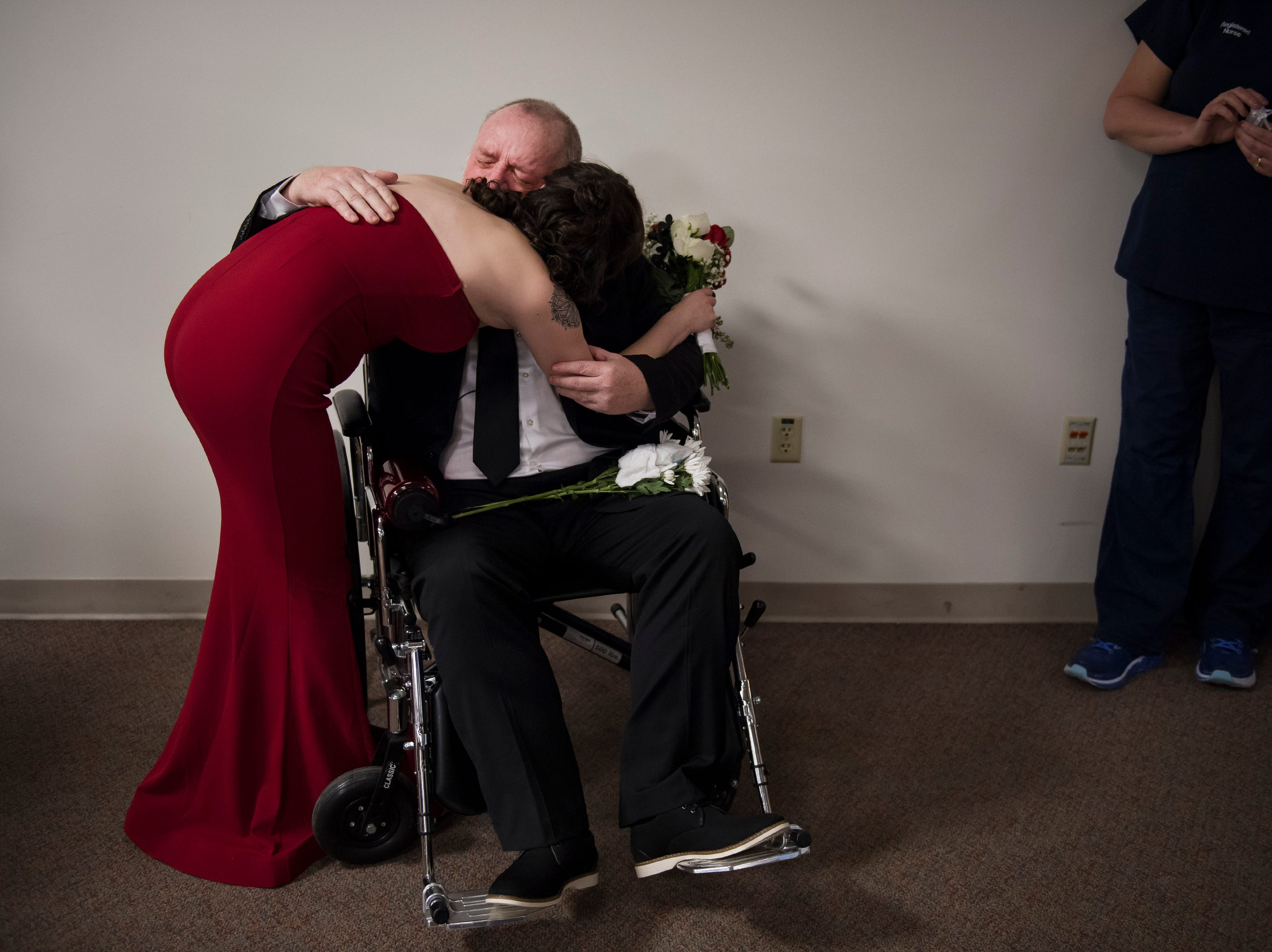 Newlywed Grace Christian hugs her father Paul Justice at the beginning of the reception of her wedding on Thursday, Feb. 14, 2019, at UCHealth Poudre Valley Hospital in Fort Collins, Colo.