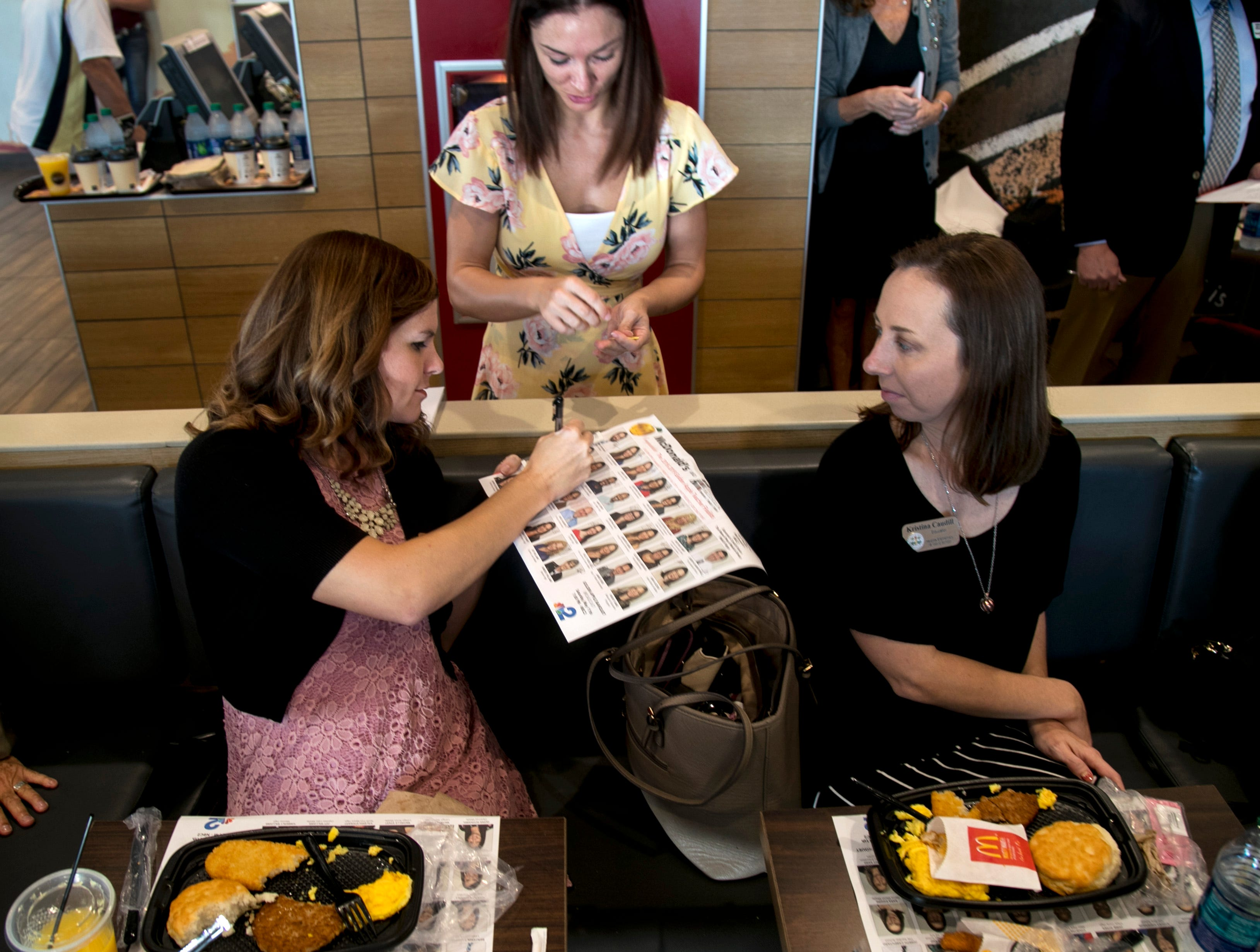 Kelley Lambert, a Golden Apple finalist from Pinewoods Elementary, signs her photo on the tray liner created with the photos of the 30 Golden Apple finalists at McDonald's in Fort Myers on Friday.