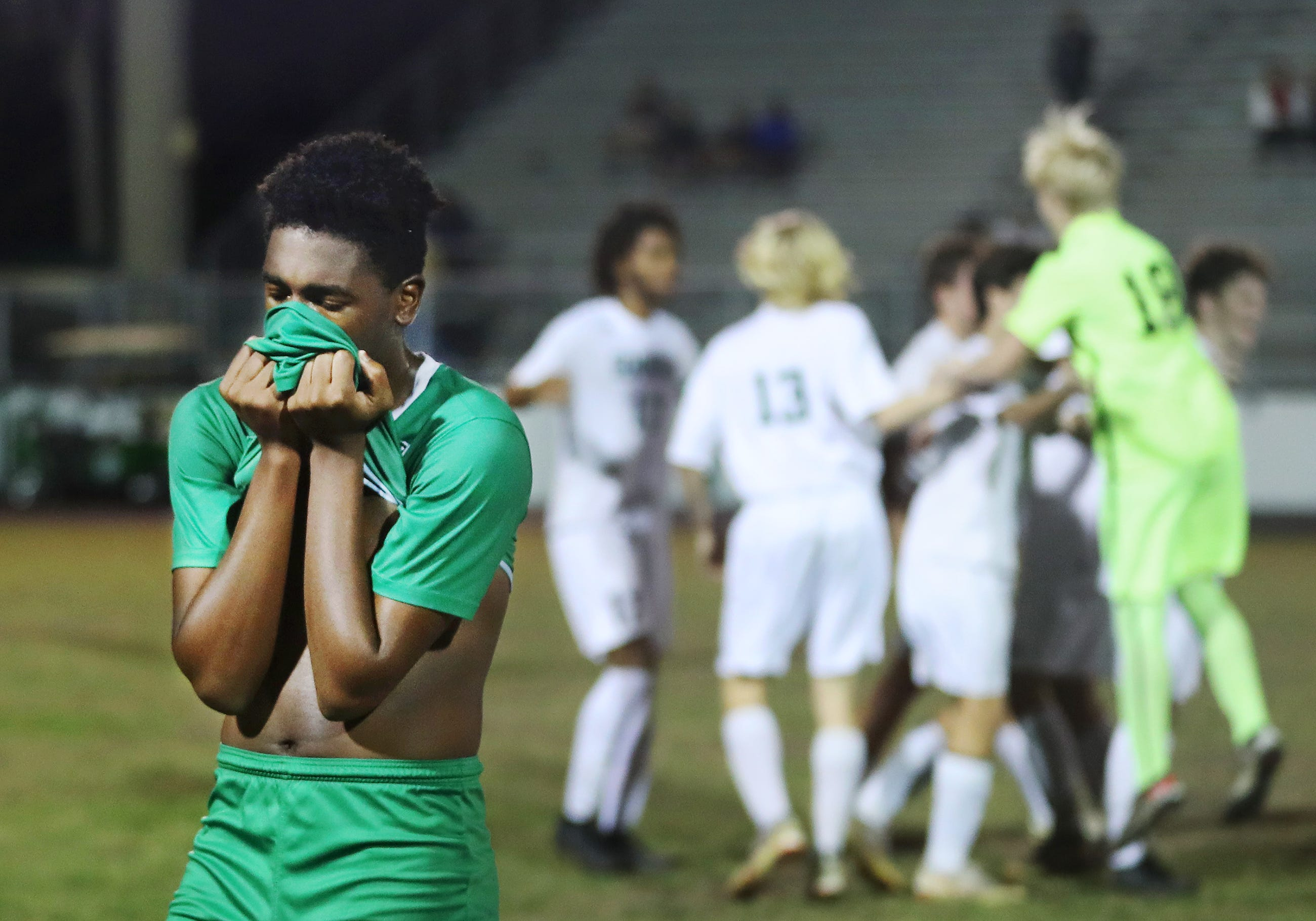 Fort Myers High School soccer player Stefan Fevrier walks off the field as Seminole players celebrate beating Fort Myers 4-3 in the Class 4A regional final recently at Fort Myers.