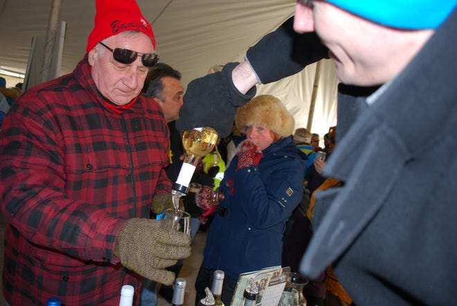 A hardy wine enthusiast gets a sample of a Parallel 44 white wine poured for him under the tent during a past Frozen Tundra Wine Fest. Guests get five free samples of wine as part of the festival, which the winery claims is the largest outdoor winter wine fest in Wisconsin.